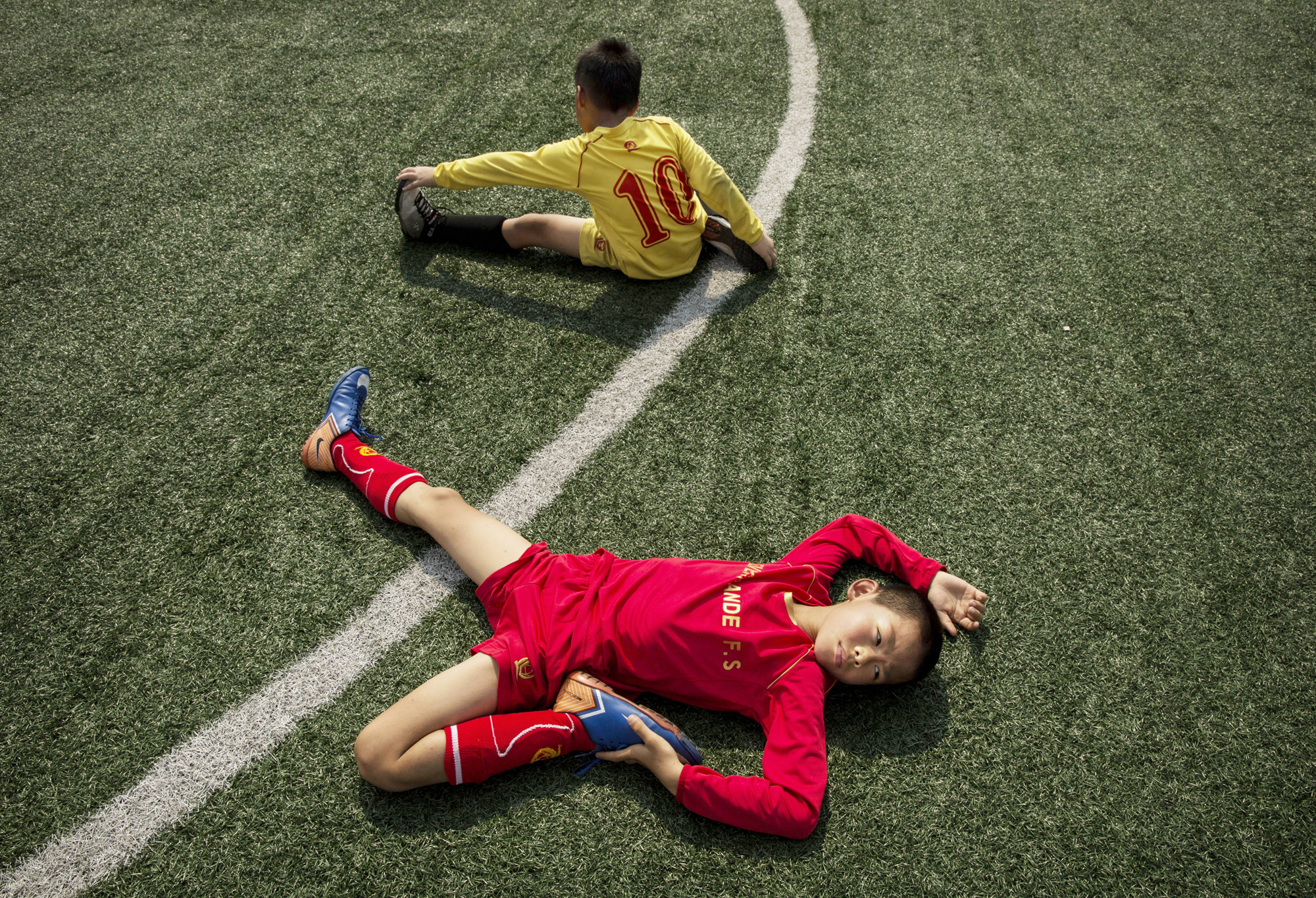 Young Chinese soccer players stretch during training at the Evergrande International Football School on June 13, 2014 near Qingyuan in Guangdong Province, China.