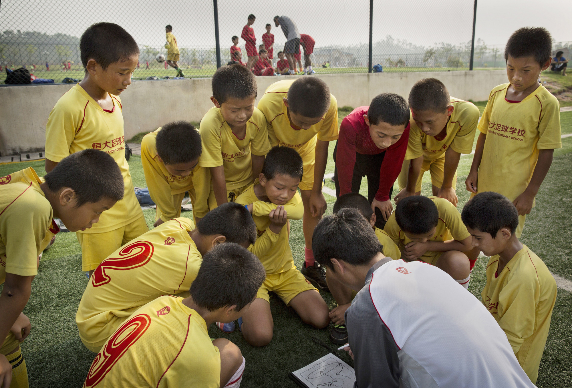 Players listen to instructions from the coach prior to a training match.