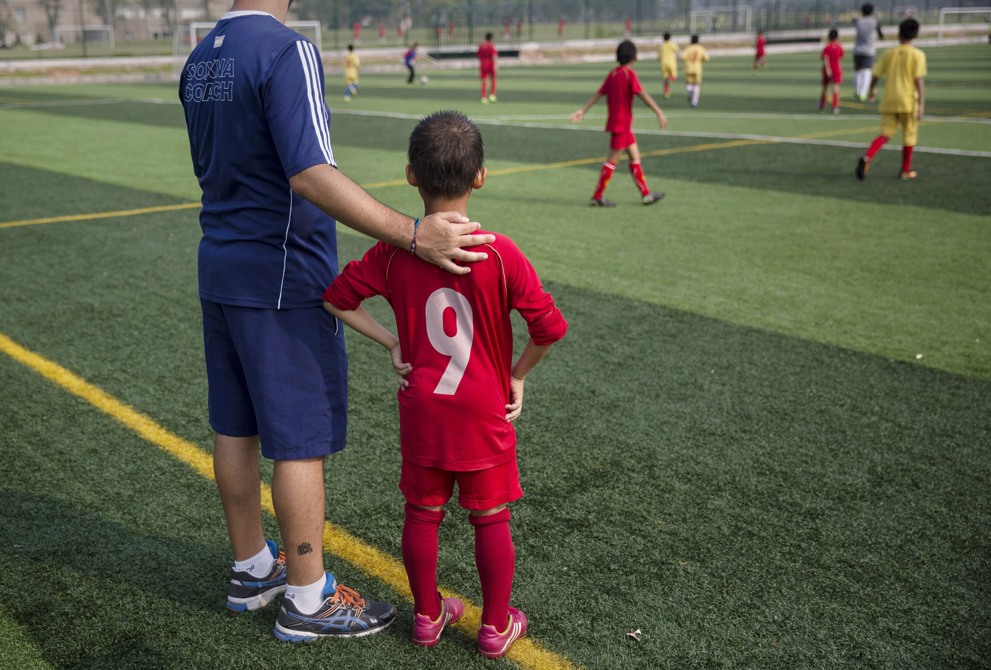 A coach from Real Madrid stands with a student during a training match.