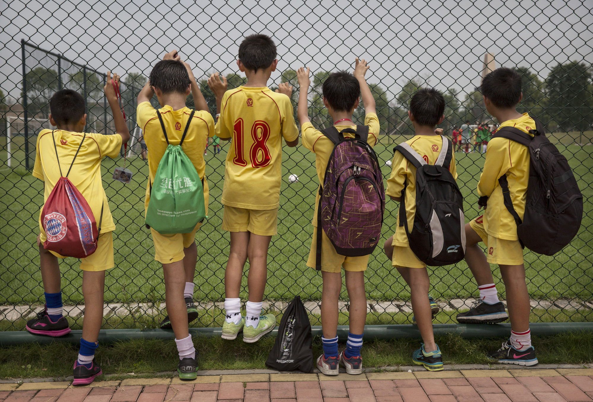 Players watch others train at the Evergrande International Football School.