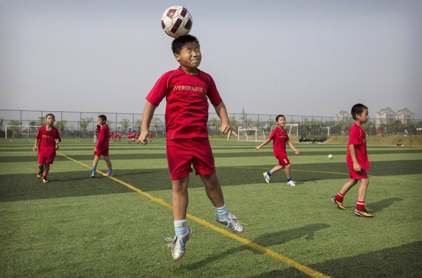 A young player leaps up to head the ball during training.