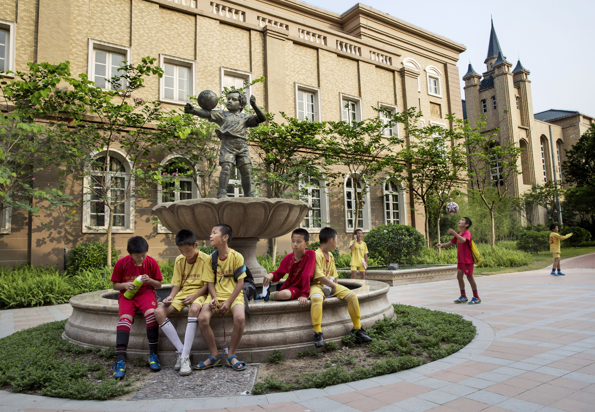 Young soccer players sit together in the campus as they wait to head to training.