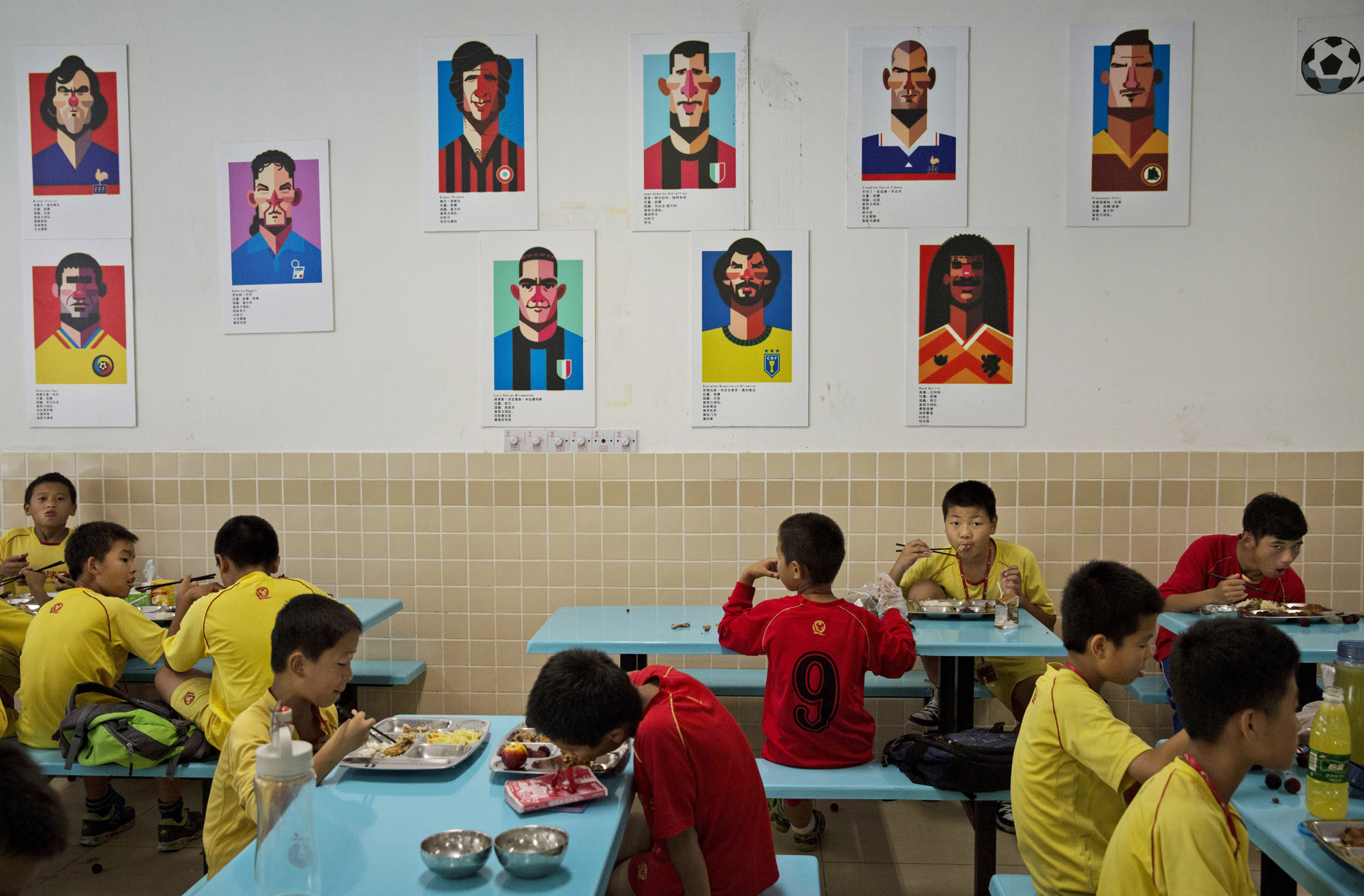Students eat lunch under caricatures of famous soccer players in the cafeteria.