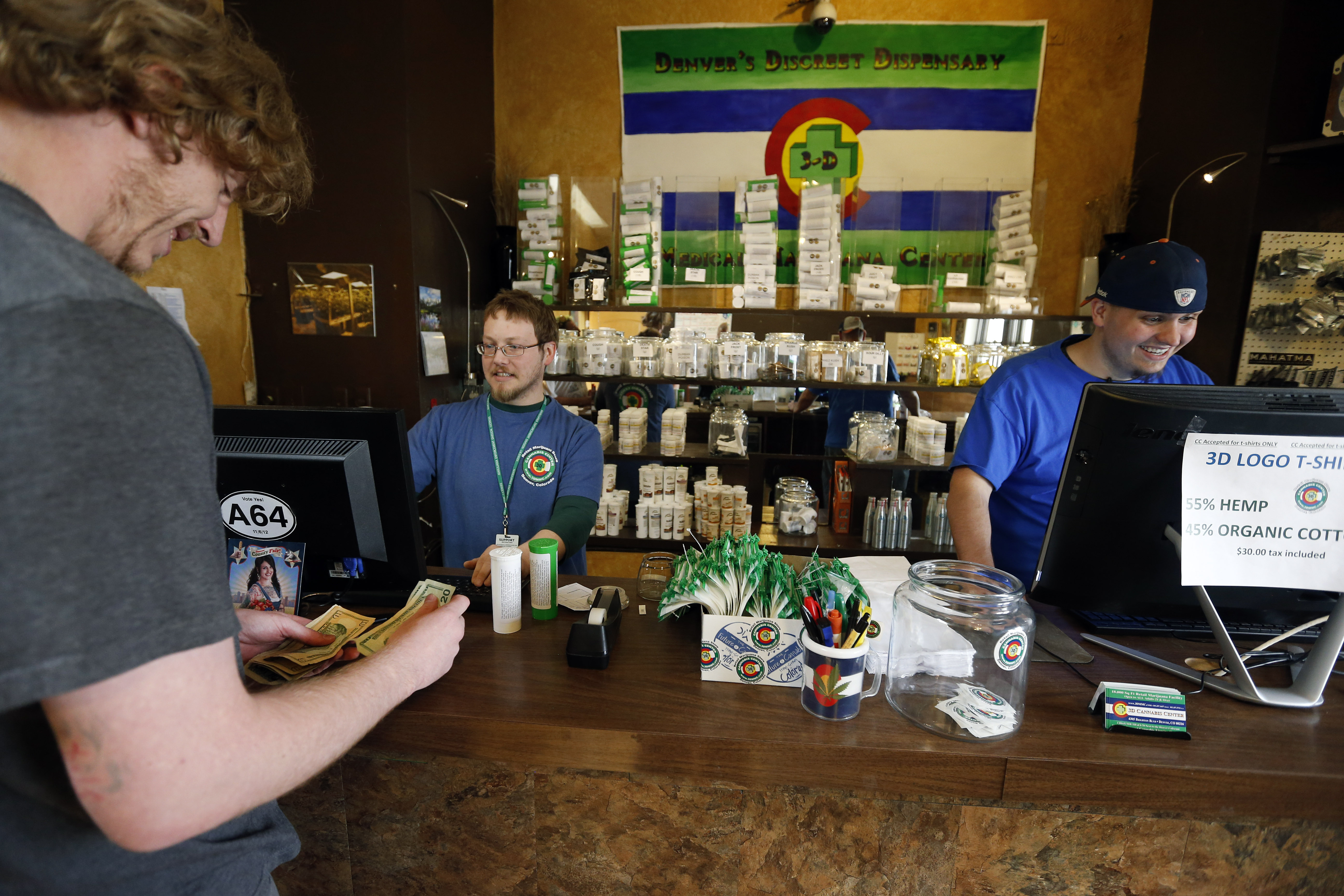 A customer pays cash for retail marijuana at 3D Cannabis Center in Denver, May 8, 2014.