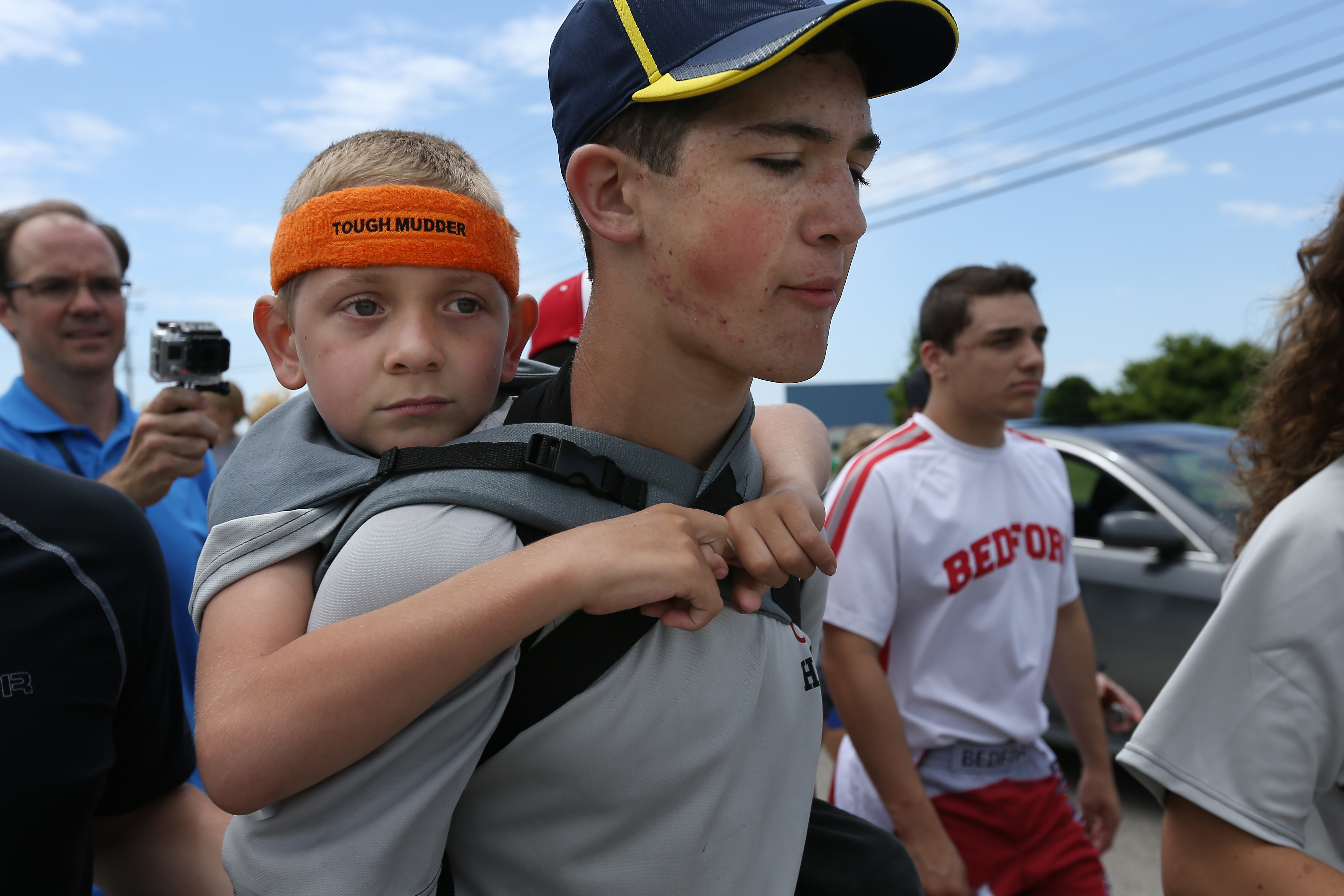 Braden Gandee, 7, rides on the back of his brother Hunter, 14, as they close in on the final miles to the University of Michigan's Bahna Wrestling Center on Sunday, June 8, 2014. Hunter carried Braden, who has cerebral palsy, 40 miles from Temperance, Mich., to Ann Arbor.