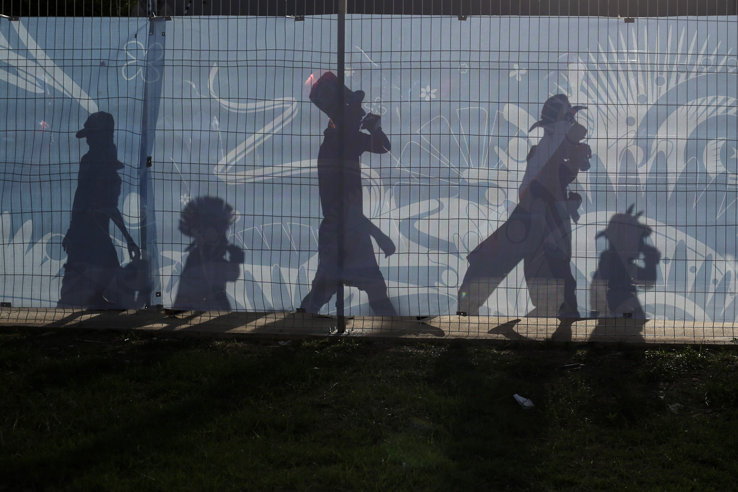 Jun. 13, 2014. The shadows of Chile soccer fans are cast on a fence outside the Arena Pantanal as they arrive to their team's World Cup match with Australia in Cuiaba, Brazil.