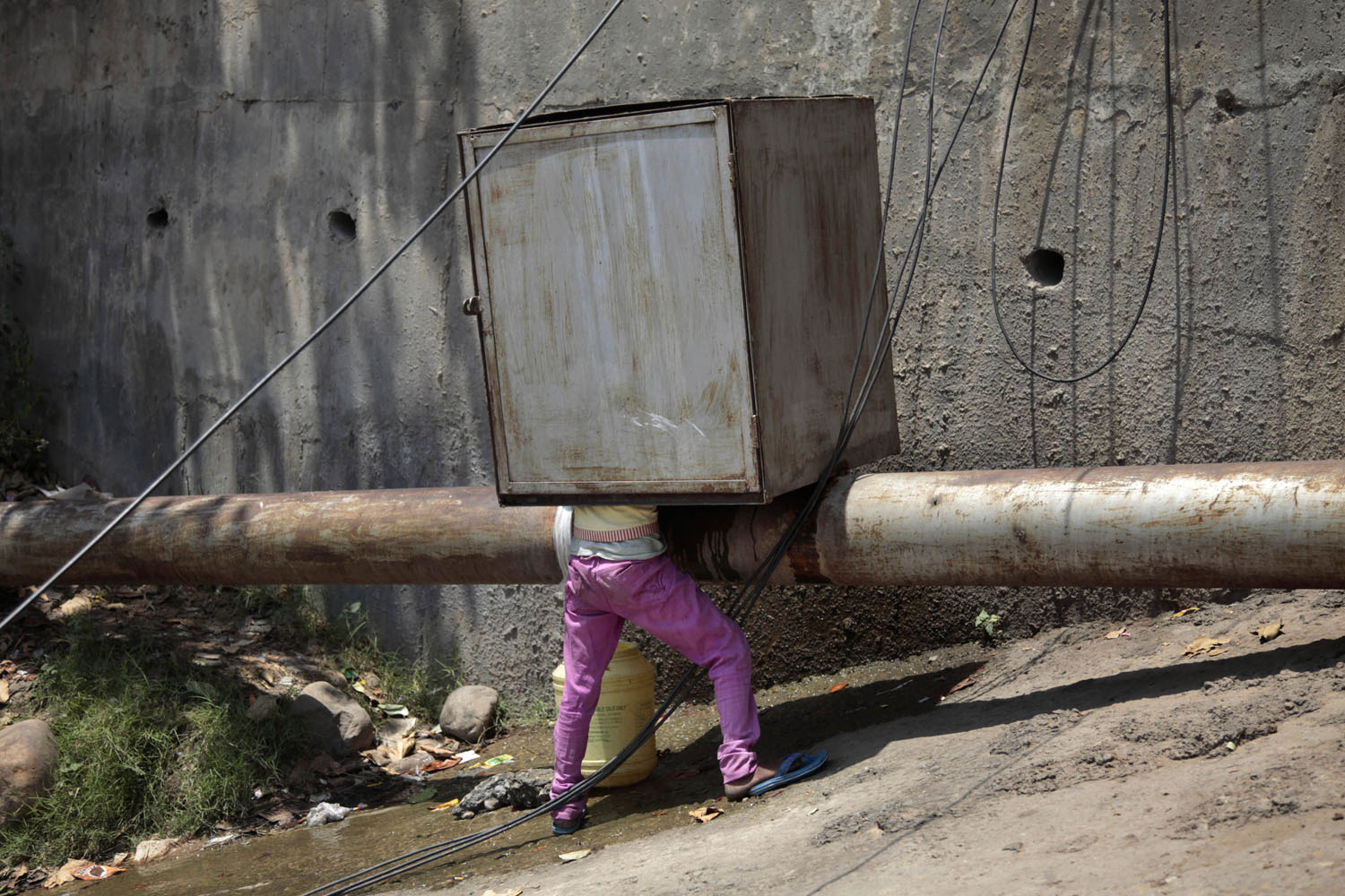 Jun. 9, 2014. A young boy collects drinking water from a leaking pipeline in the outskirts of Jammu, India.