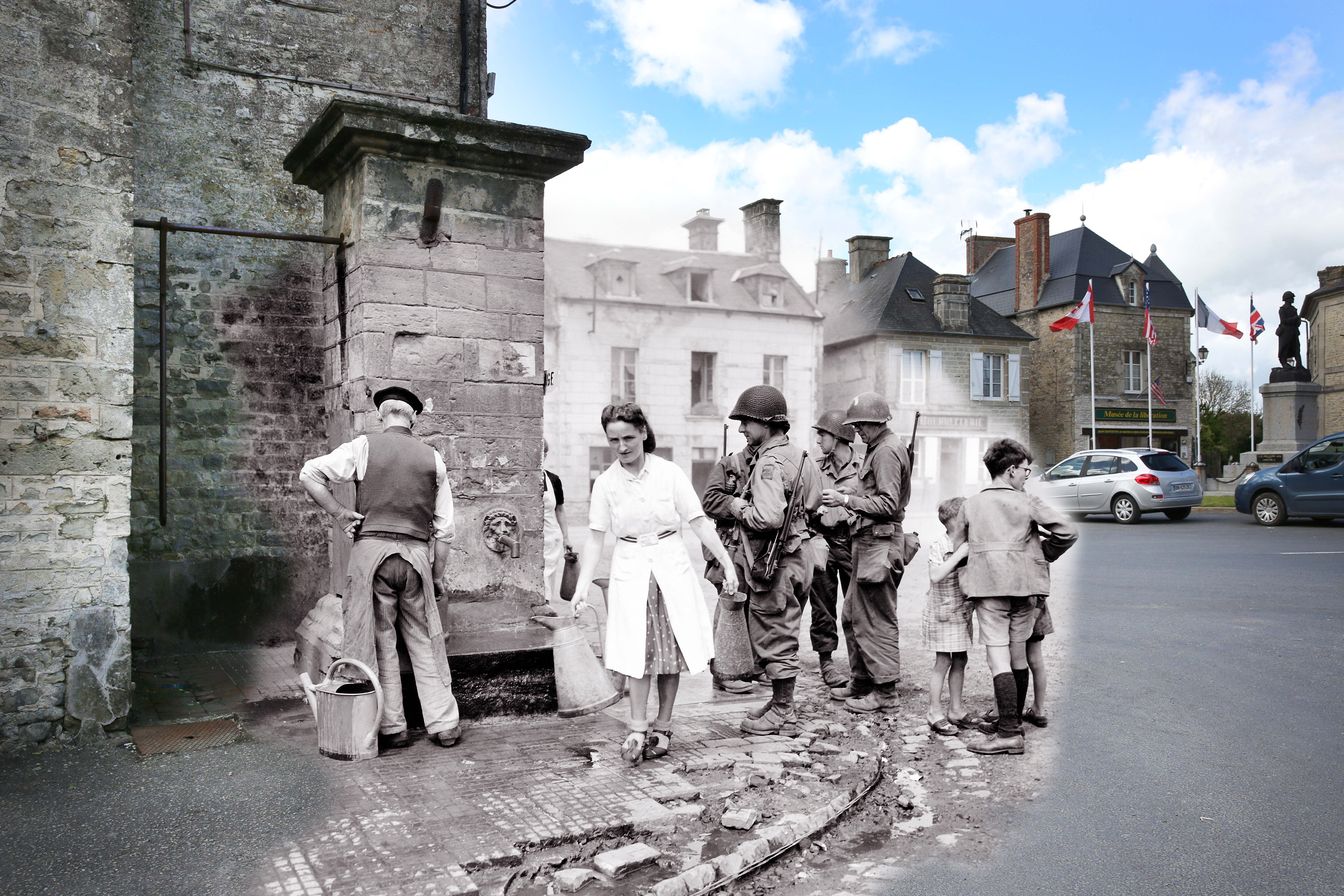 A view of the old village fountain on May 7, 2014 in Sainte Marie du Mont, France. Overlay: A woman walks away with two pitchers while three children are watching the scene, and an old man fetches water next to a GI expecting to wash his bowls on June 12, 1944.