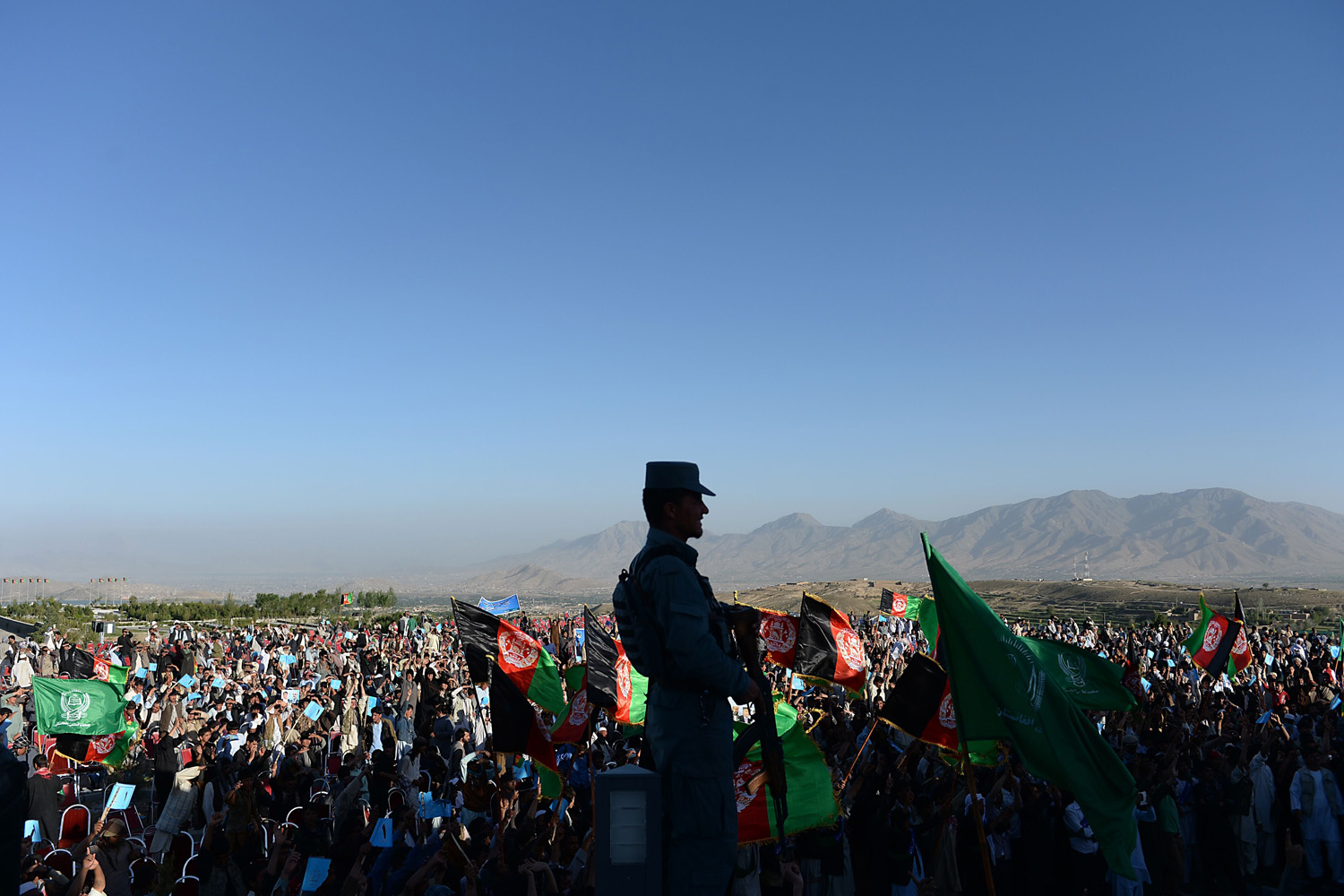 Jun. 9, 2014. An Afghan policeman keeps watch as supporters of presidential candidate Abdullah Abdullah cheer during an election campaign rally in Paghman district of Kabul province.