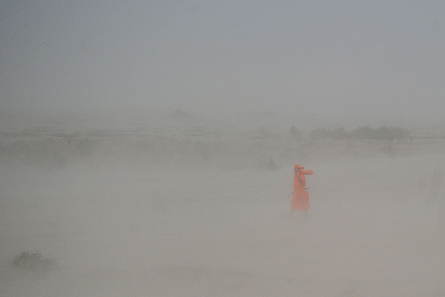 Jun. 23, 2014. An Indian Hindu sadhu (holy man) walks through a dust storm at the Sangam, the confluence of the rivers Ganges, Yamuna and mythical Saraswati, in Allahabad.