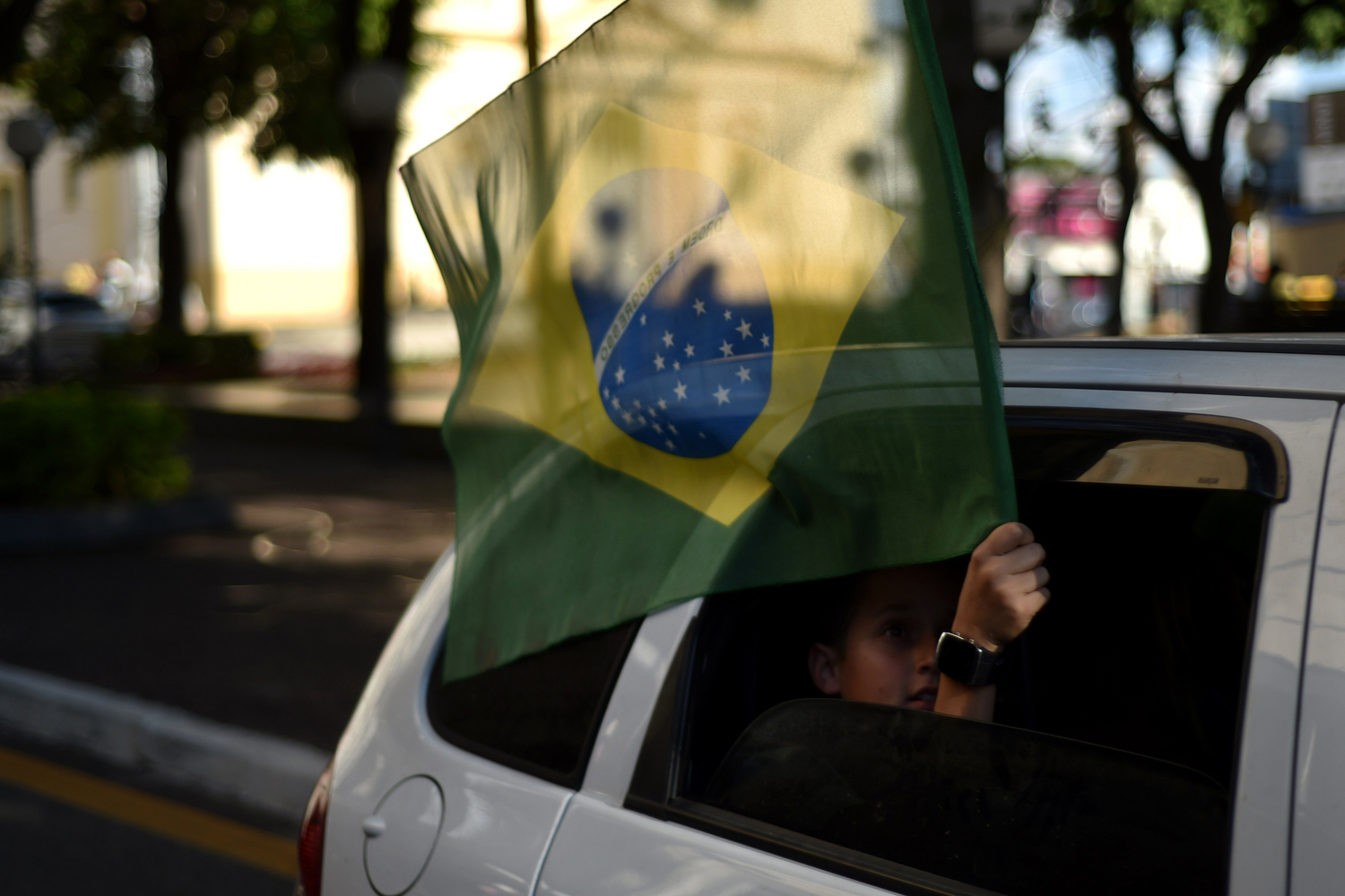 Jun. 12, 2014. A supporters of the Brazilian national football team holds a Brazilian flag out of a car window in Itu prior to the opening match of the 2014 FIFA World Cup between Brazil and Croatia being played at the Corinthians Arena in Sao Paulo.