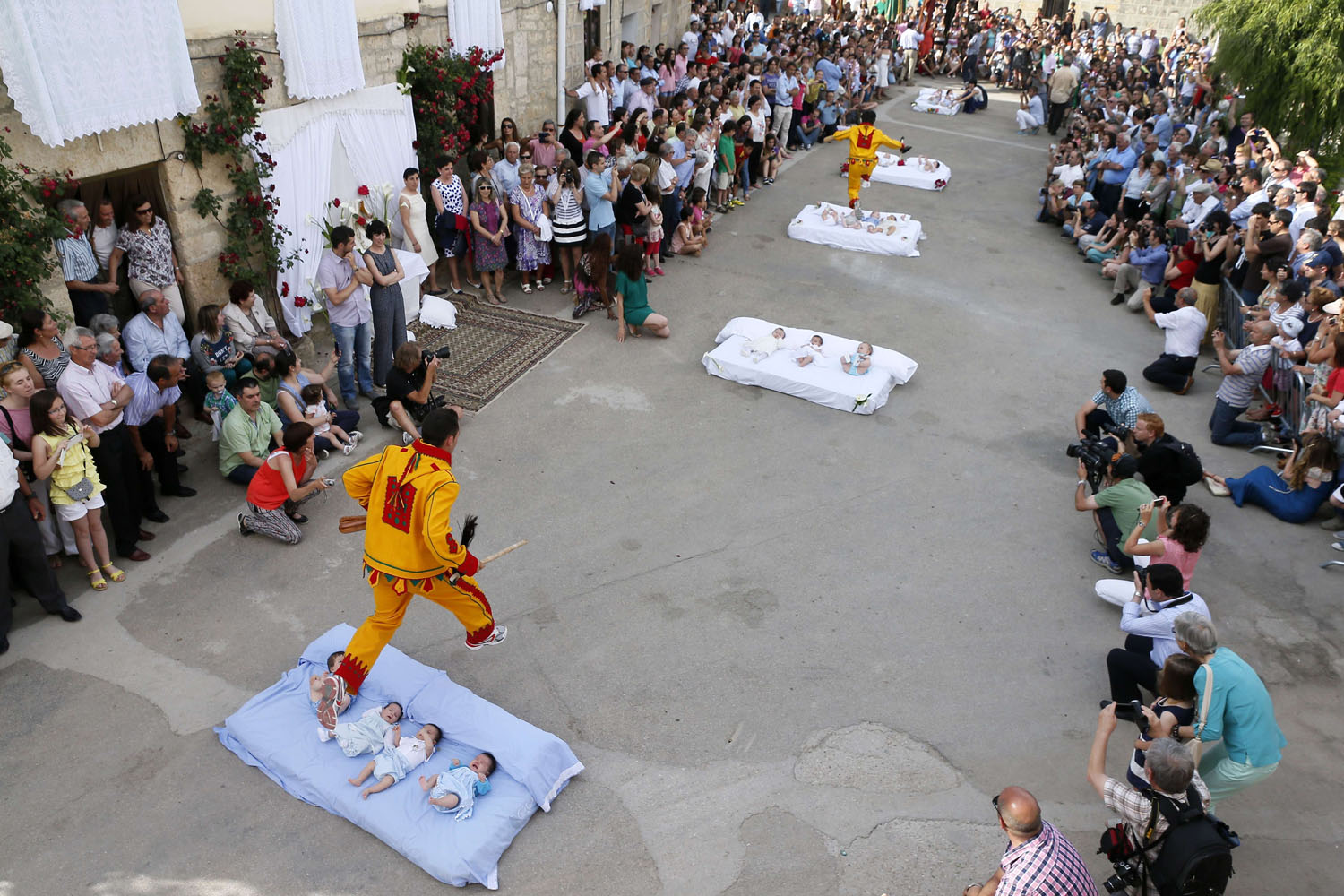 Jun. 22, 2014. A man dressed up as the devil jumps over babies lying on a mattress in the street during 'El Colacho', the 'baby jumping festival' in the village of Castrillo de Murcia, near Burgos.