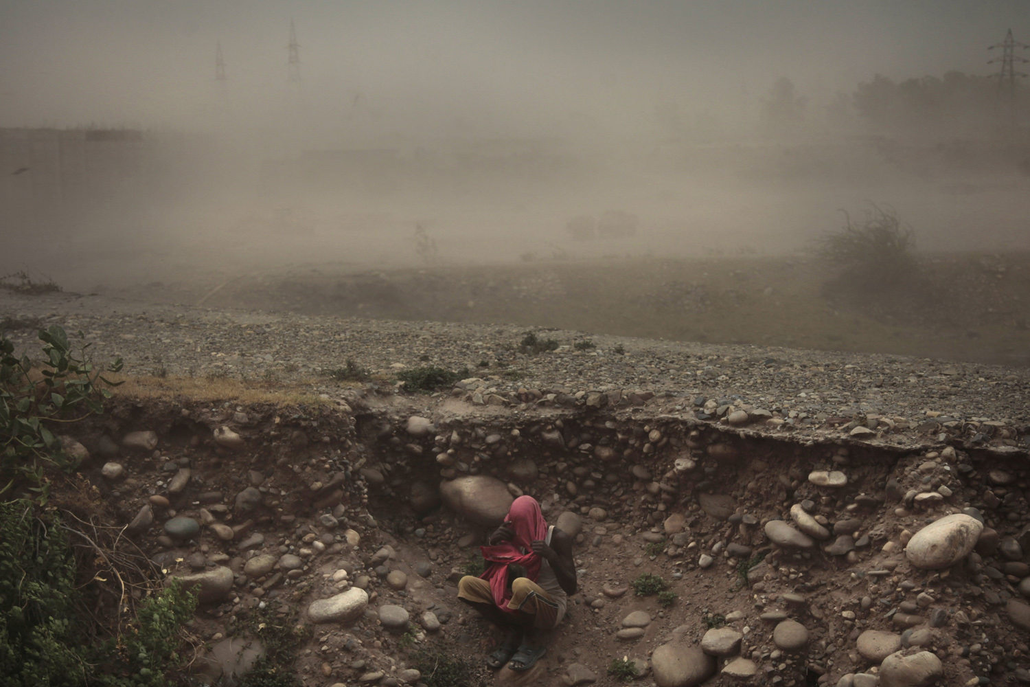 Jun. 16, 2014. An Indian man sits beneath the road level with his face covered during a powerful dust storm in Jammu, India.