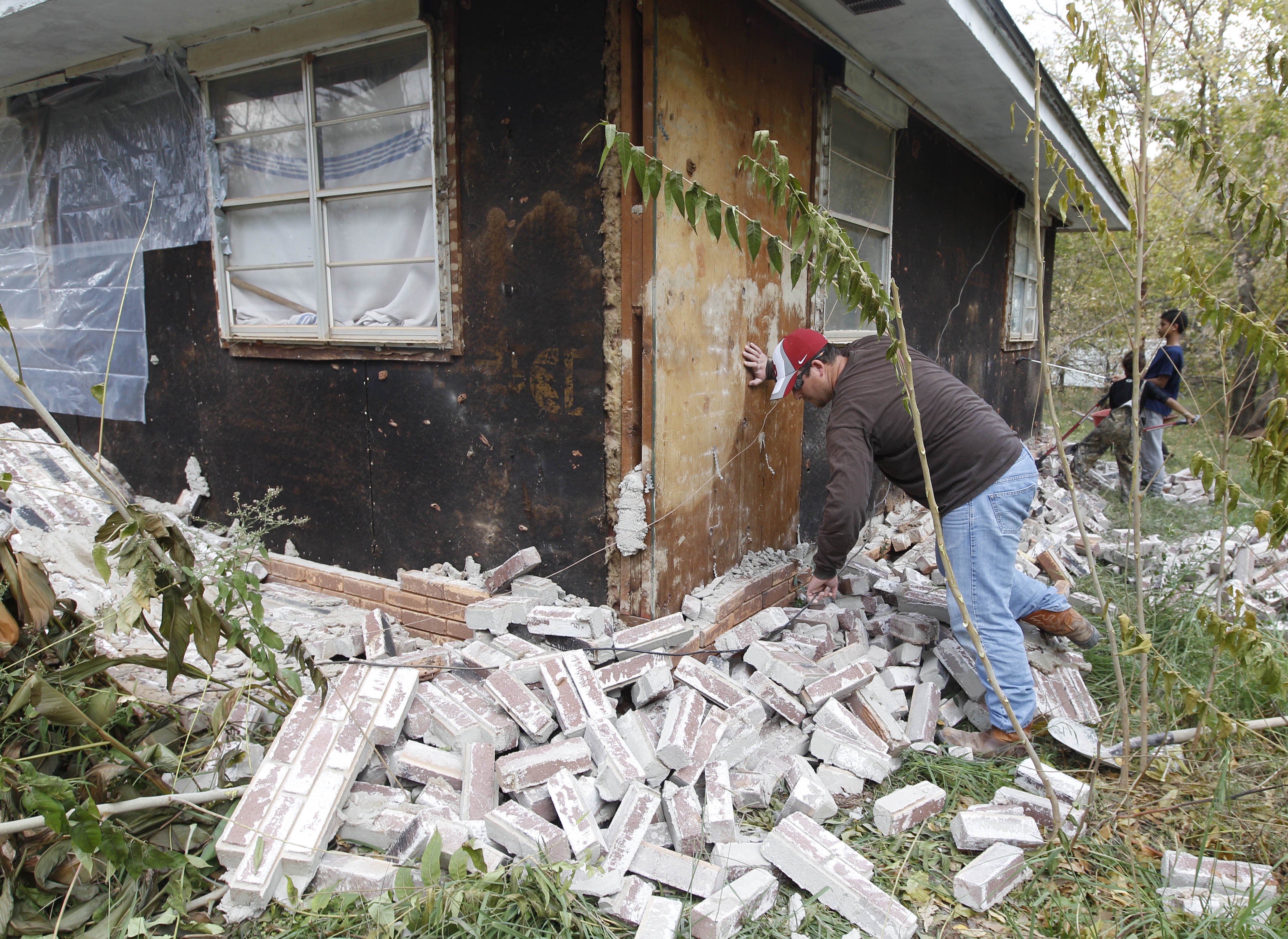 Chad Devereaux examines bricks that fell from three sides of his in-laws' home in Sparks, Okla., on Nov. 6, 2011, following two earthquakes that hit the area.