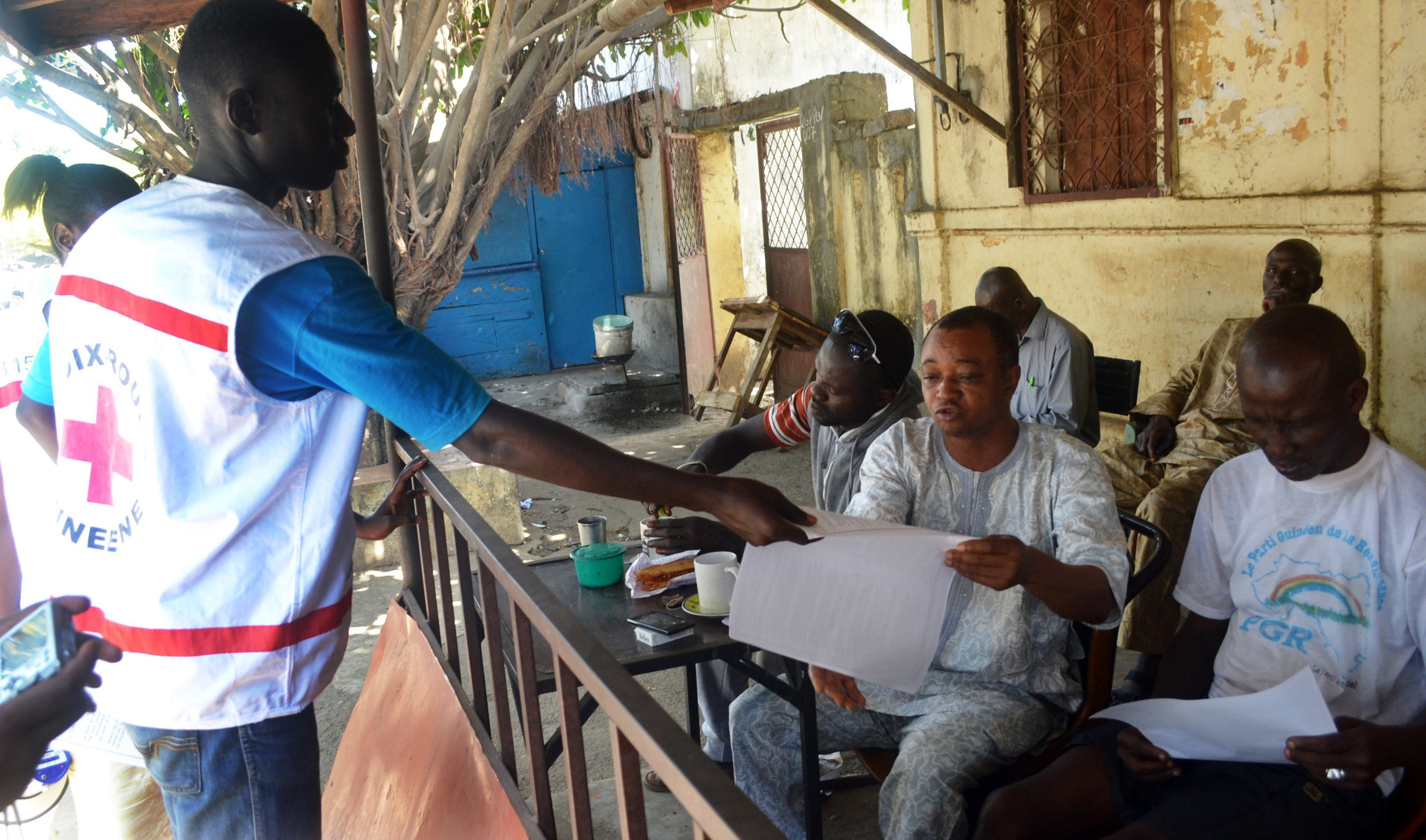 Members of the Guinean Red Cross distribute information leaflets during an awareness campaign on the Ebola virus on April 11, 2014 in Conakry, Guinea.