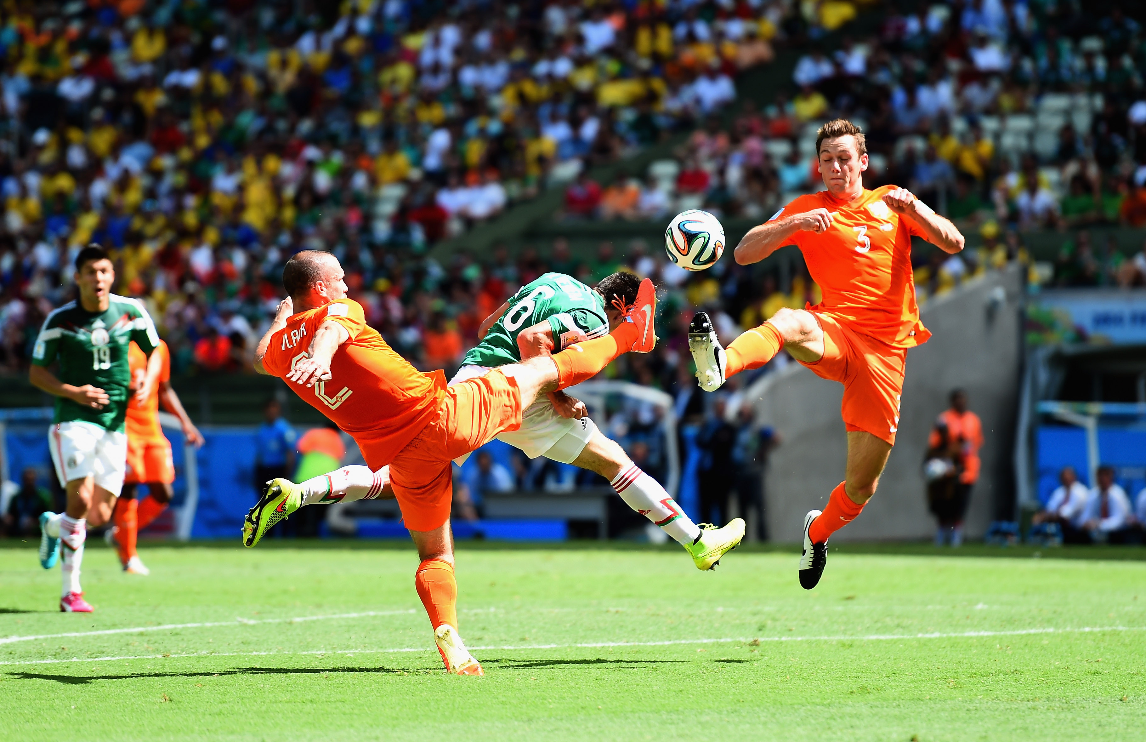Ron Vlaar and Stefan De Vrij of Netherlands battles with Hector Herrera of Mexico during the 2014 FIFA World Cup on June 29 in Fortaleza, Brazil.