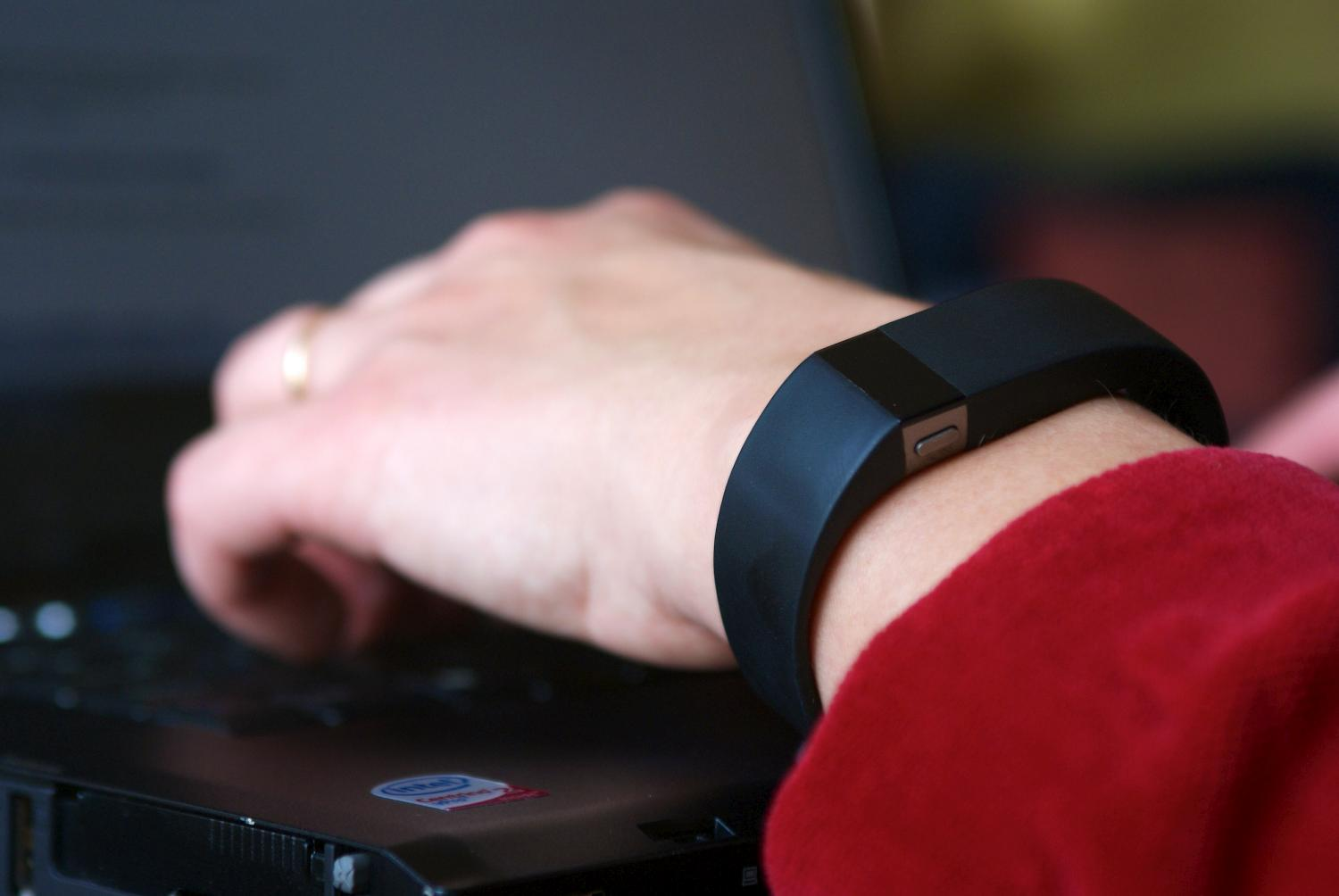 A person wearing a Fitbit fitness band types on a laptop