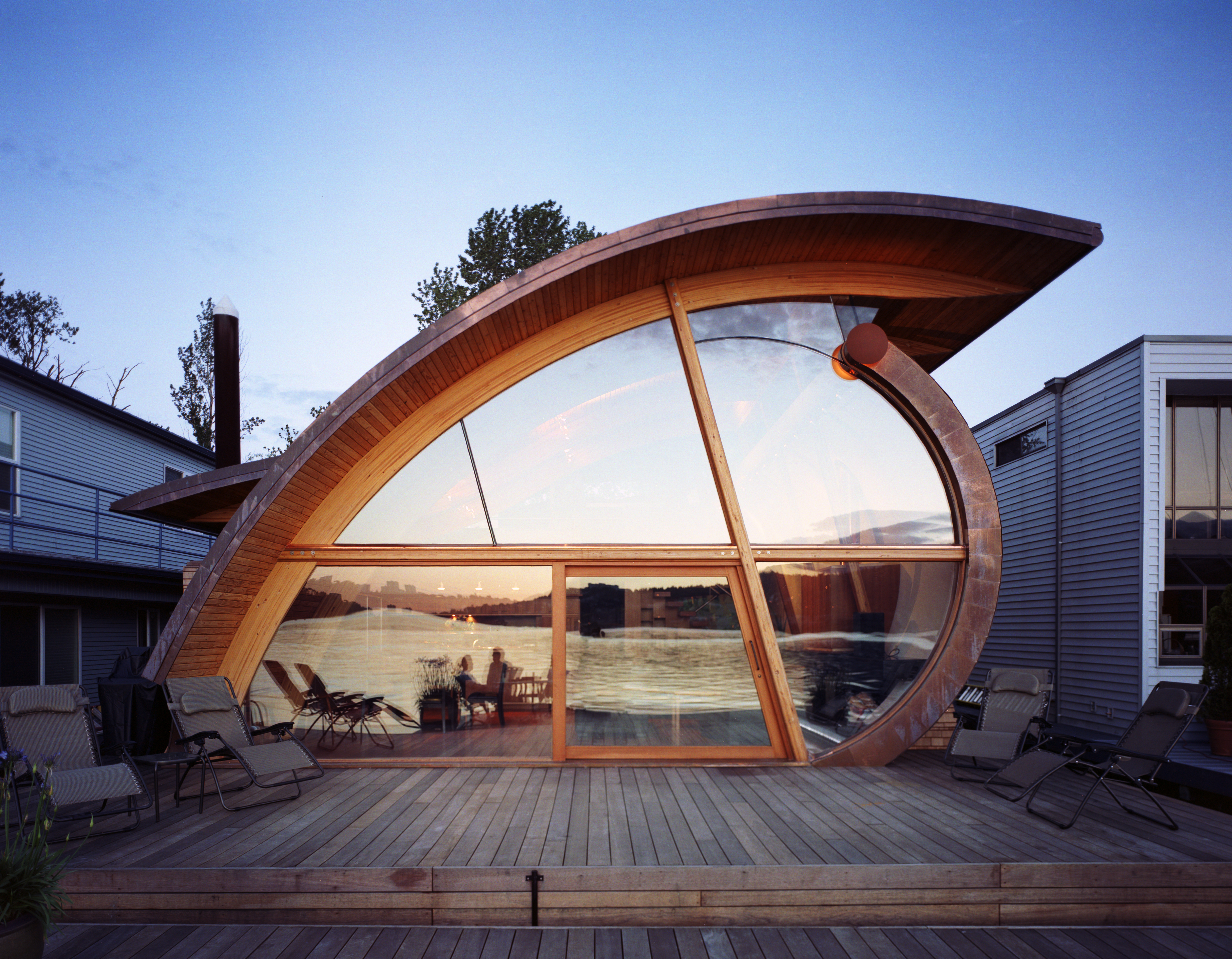 The Fennel House, designed by Robert Harvey Oshatz, floats on Portland's Willamette River. Its curved form, reflecting the ripples of the water, is made with Glulam wood beams and sits on a floating platform.