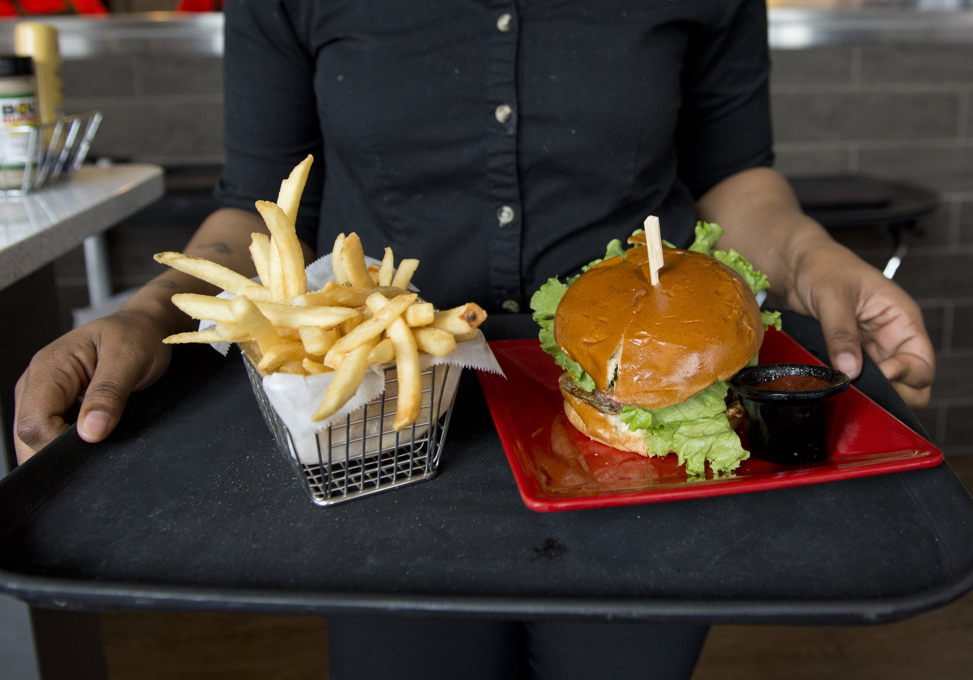A server carries a tray with a hamburger and french fries at Bolt Burgers in Washington, DC on February 25, 2014.