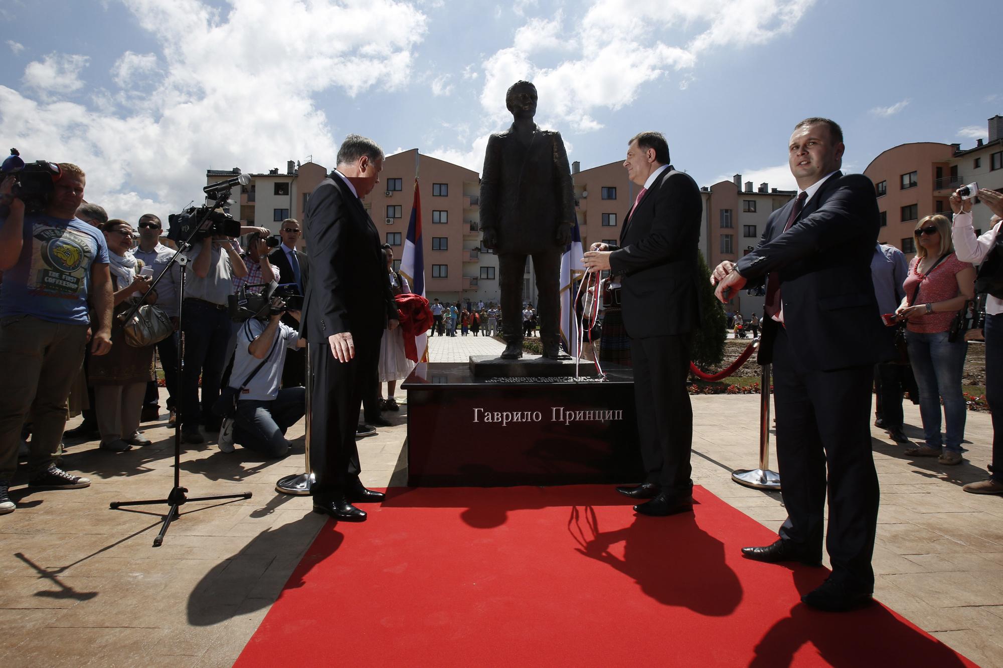 Member of Bosnian Tripartite Presidency Nebojsa Radmanovic, left, President of Republika Srpska Milorad Dodik , center, and local mayor Ljubisa Cosic, right, uncover a statue of Gavrilo Princip during ceremony of unveiling in Istocno Sarajevo, June 27, 2014.