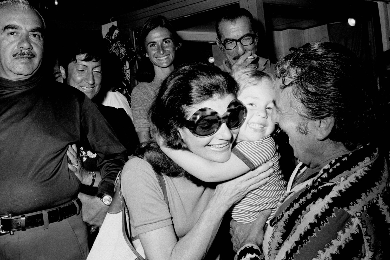 Former First Lady Jacqueline Kennedy Onassis gets a hug from a young fan in Capri, Italy in 1973.