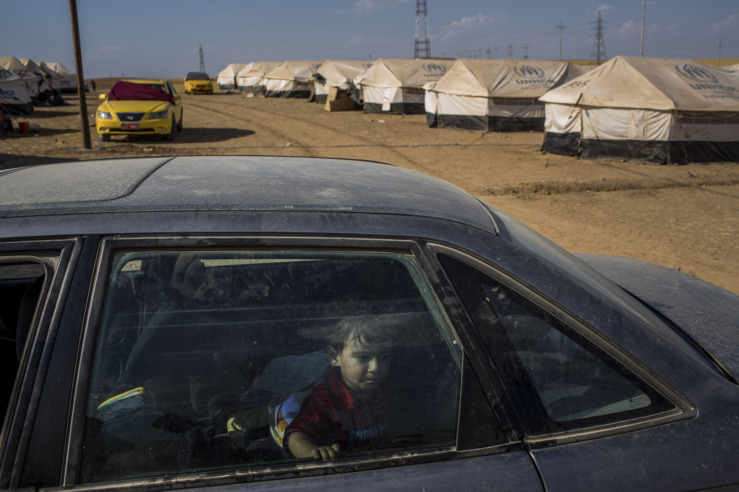 June 18, 2014. A child sits in his family's car at a United Nations-run camp between Mosul and Irbil, Iraq.