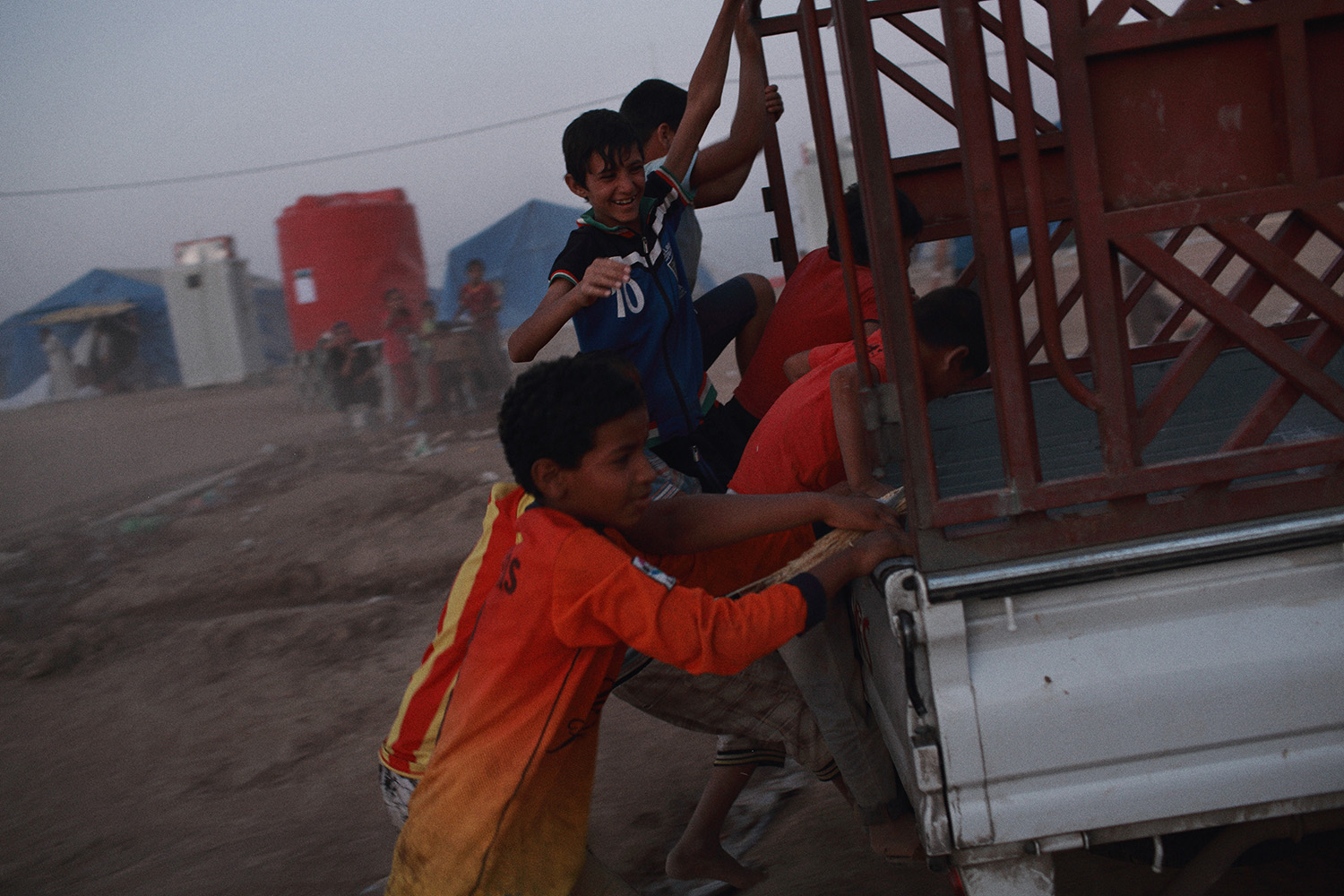 June 20, 2014. Collecting bread rolls from a truck becomes a game for children at the Khazar refugee camp between Erbil and Mosul where many residents from Mosul and it's surrounds have found refuge following the city's takeover by Islamist militants of the Islamic State of Iraq and the Levant (ISIL) group.