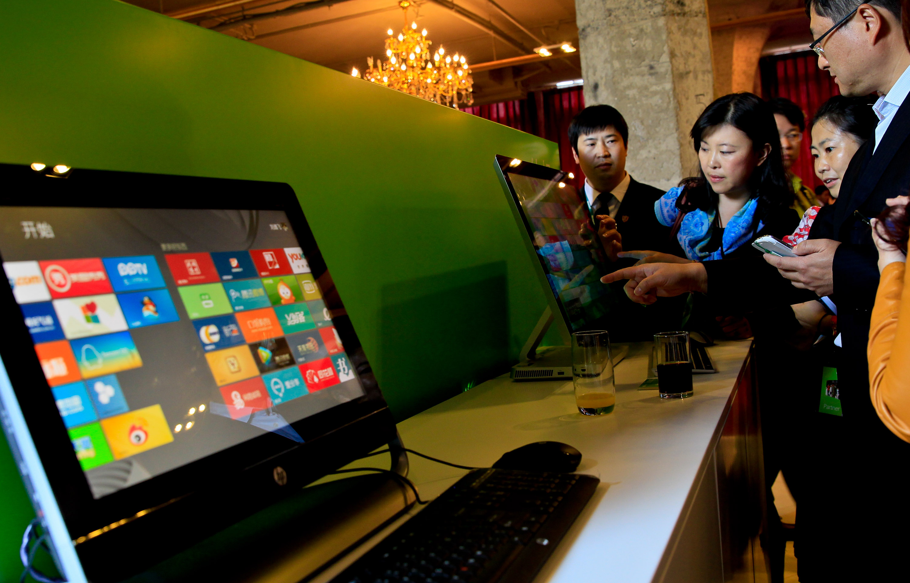 Guests try out the Microsoft Windows 8 operation system on touchable screens of desktop computers during the preview show of the new operation system and tablet computer Surface in Shanghai, China, Oct. 23, 2012.