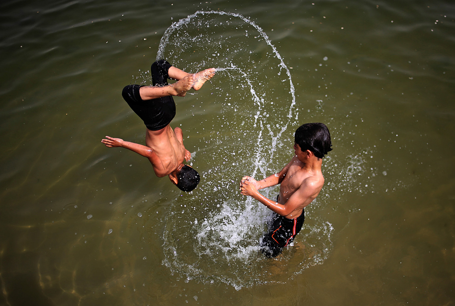 Two Palestinian brothers escape the heat by playing in the water in  the west of Gaza City on  June 4, 2014.