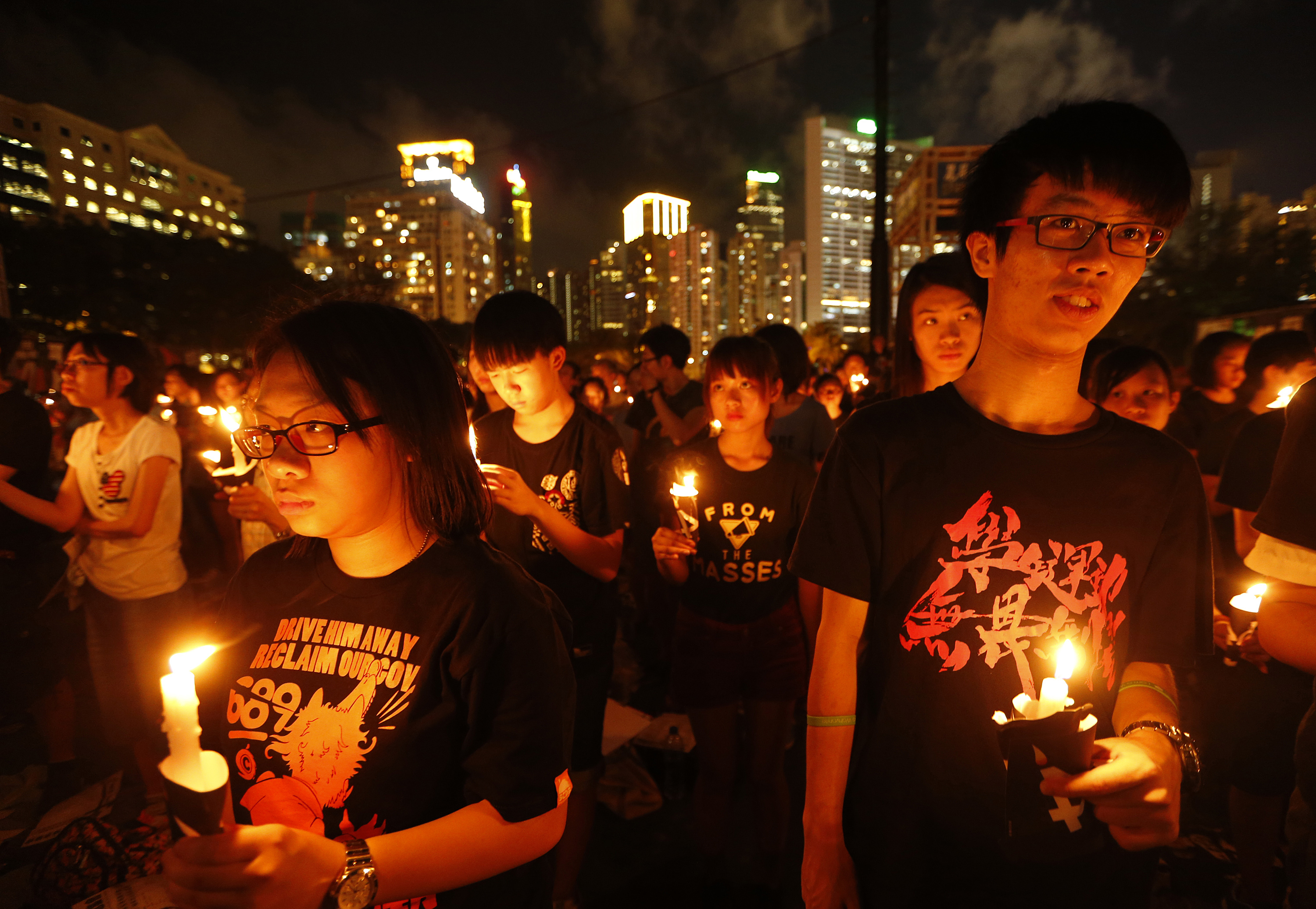 Participants hold candles as they join tens of thousands of people attending a candlelight vigil at Victoria Park in Hong Kong on June 4, 2014