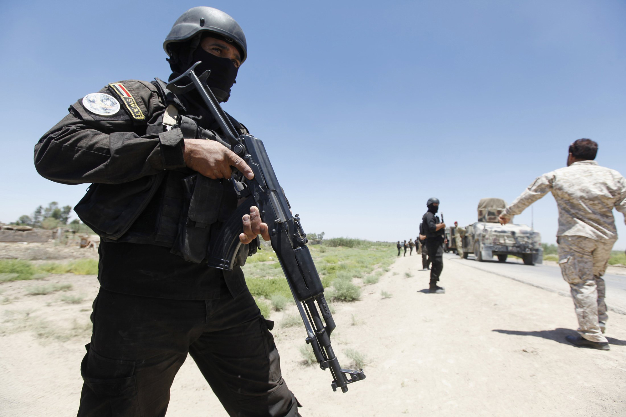 Members of the Iraqi security forces take their positions during an intensive security deployment west of Baghdad, June 24, 2014.