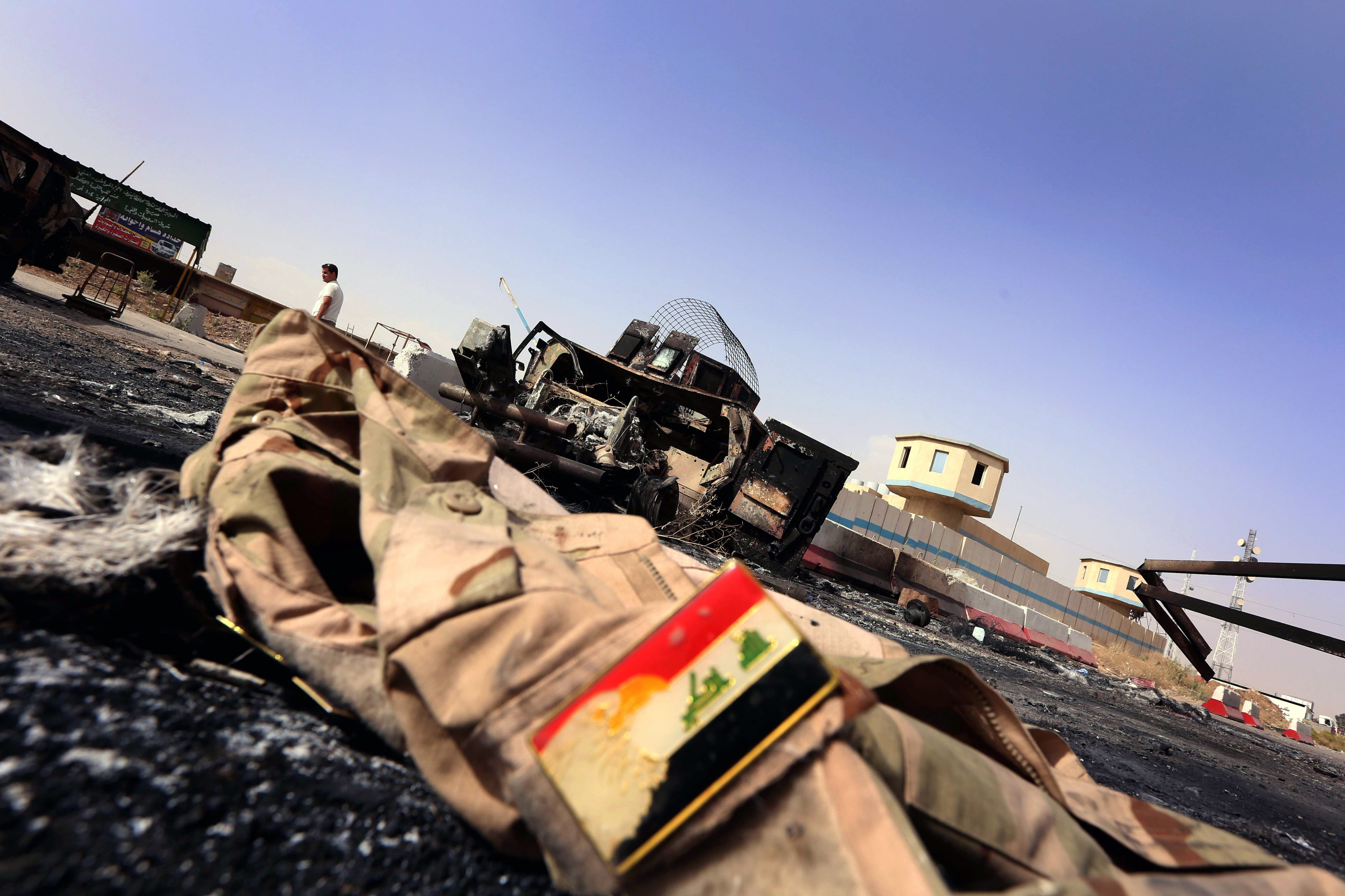 A jacket belonging to an Iraqi Army uniform lies on the ground in front of the remains of a burnt out Iraqi army vehicle close to the Kukjali Iraqi Army checkpoint, some 10km east of the northern city of Mosul, Iraq on June 11, 2014.