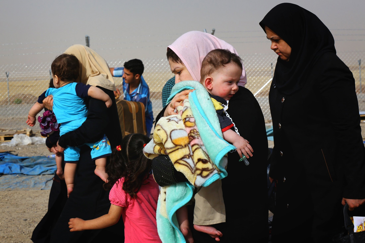 Families fleeing the violence in the Iraqi city of Mosul arrive at a checkpoint on the outskirts of Erbil, in Iraq's Kurdistan region June 12.