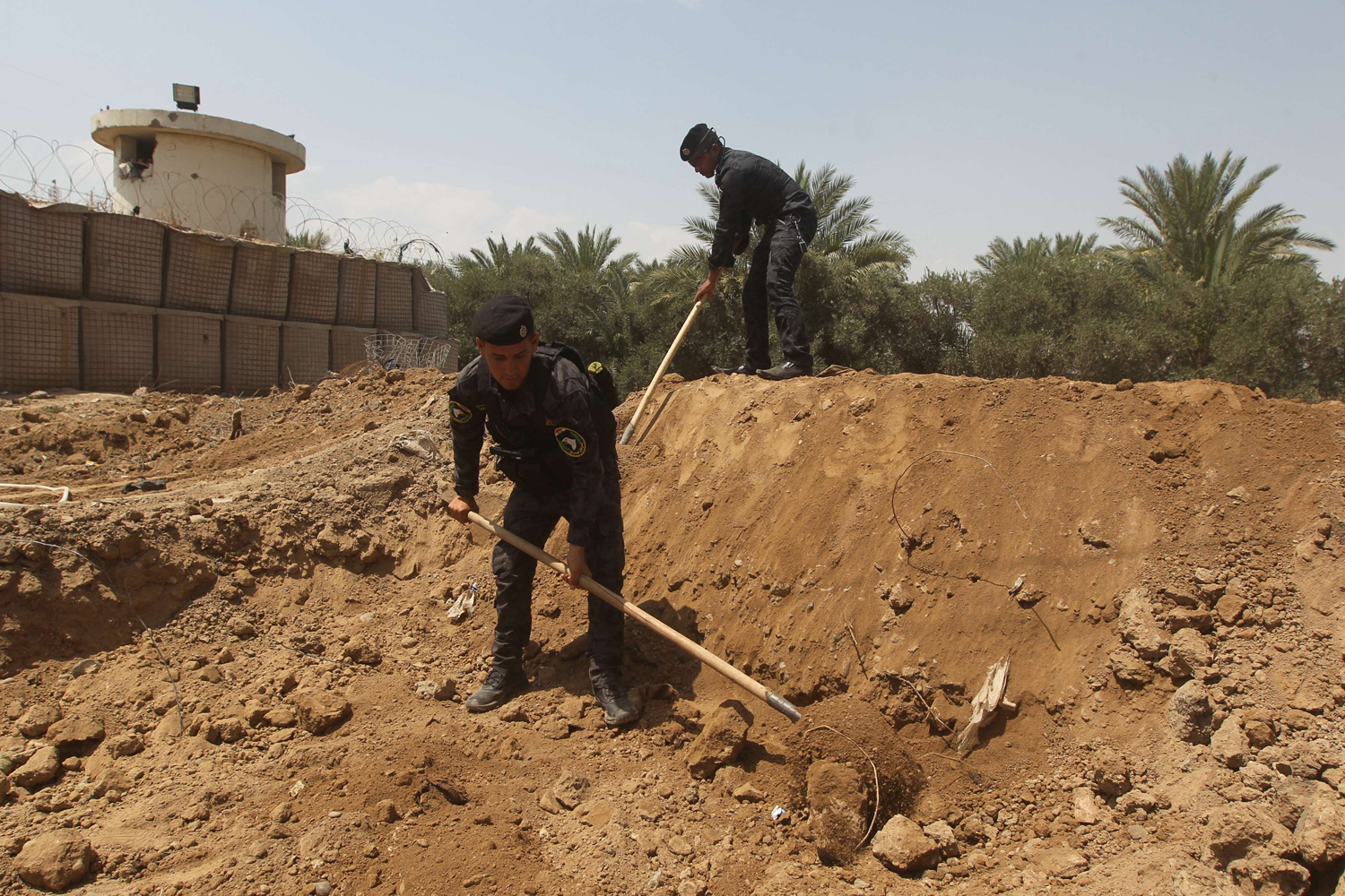 Iraqi policemen dig trenches at checkpoint in the Iraqi town of Taji, at the entrance of Baghdad, on June 13, as security forces are bolstering defenses in the capital.
