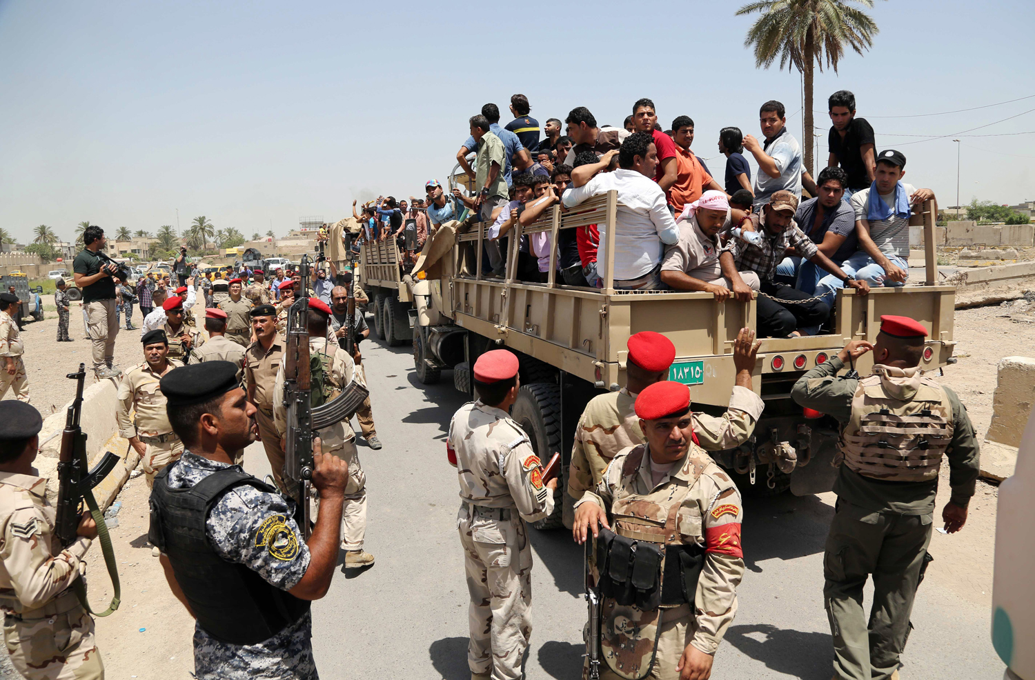 Men board military trucks to join the Iraqi army at the main recruiting center in Baghdad on June 14, after authorities urged Iraqis to help battle insurgents.