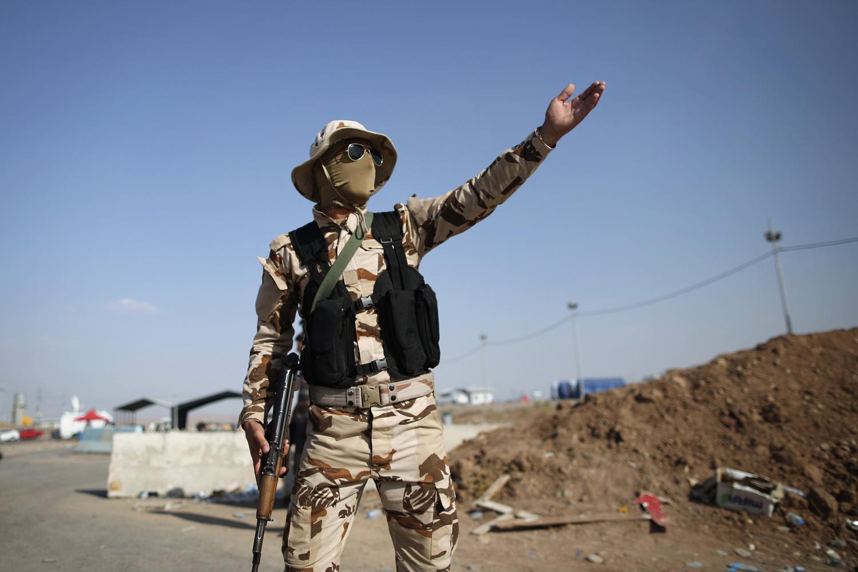 Peshmerga military direct traffic at a Kurdish checkpoint on June 14, in Kalak.
