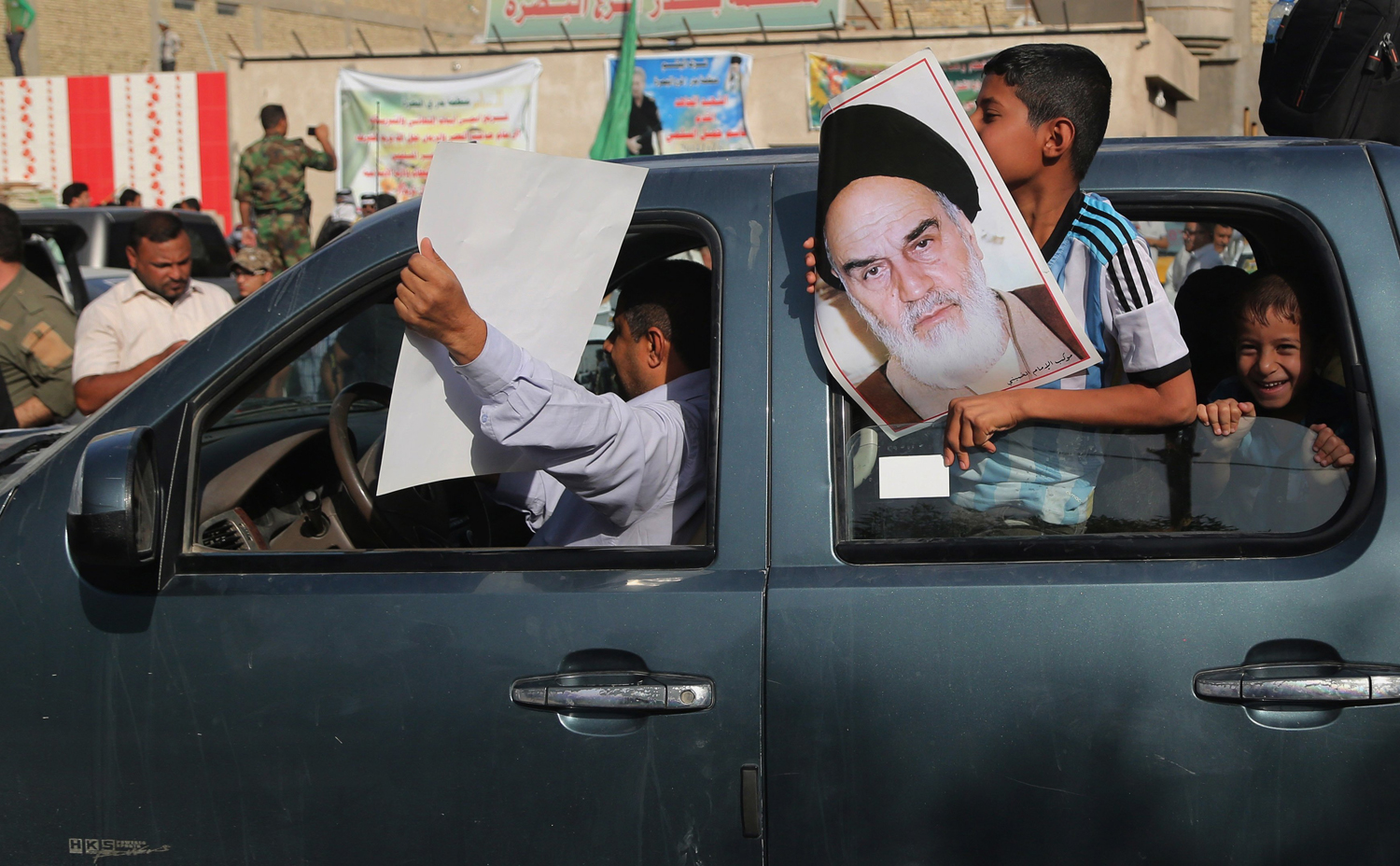 People hold posters showing Iran's spiritual leaders Ayatollah Khomeini, while Iraqi Shiite fighters deploy with their weapons in Basra,  June 14.