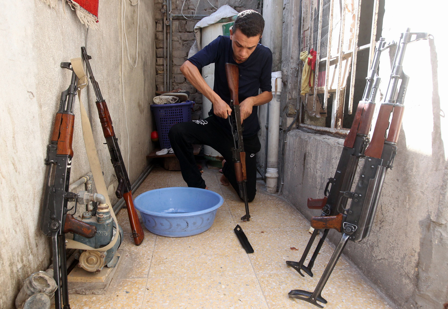 A Shiite man cleans weapons as he gets ready to defend his Sadr City district in case of an attack by Sunni extremists, on June 13 in Baghdad.