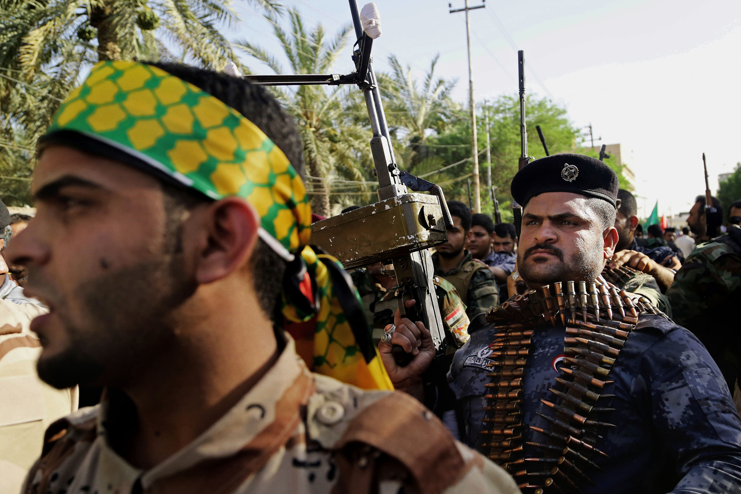 Shiite tribal fighters raise their weapons and chant slogans against the al-Qaida-inspired Islamic State of Iraq and Syria (ISIS) in Basra, June 16.