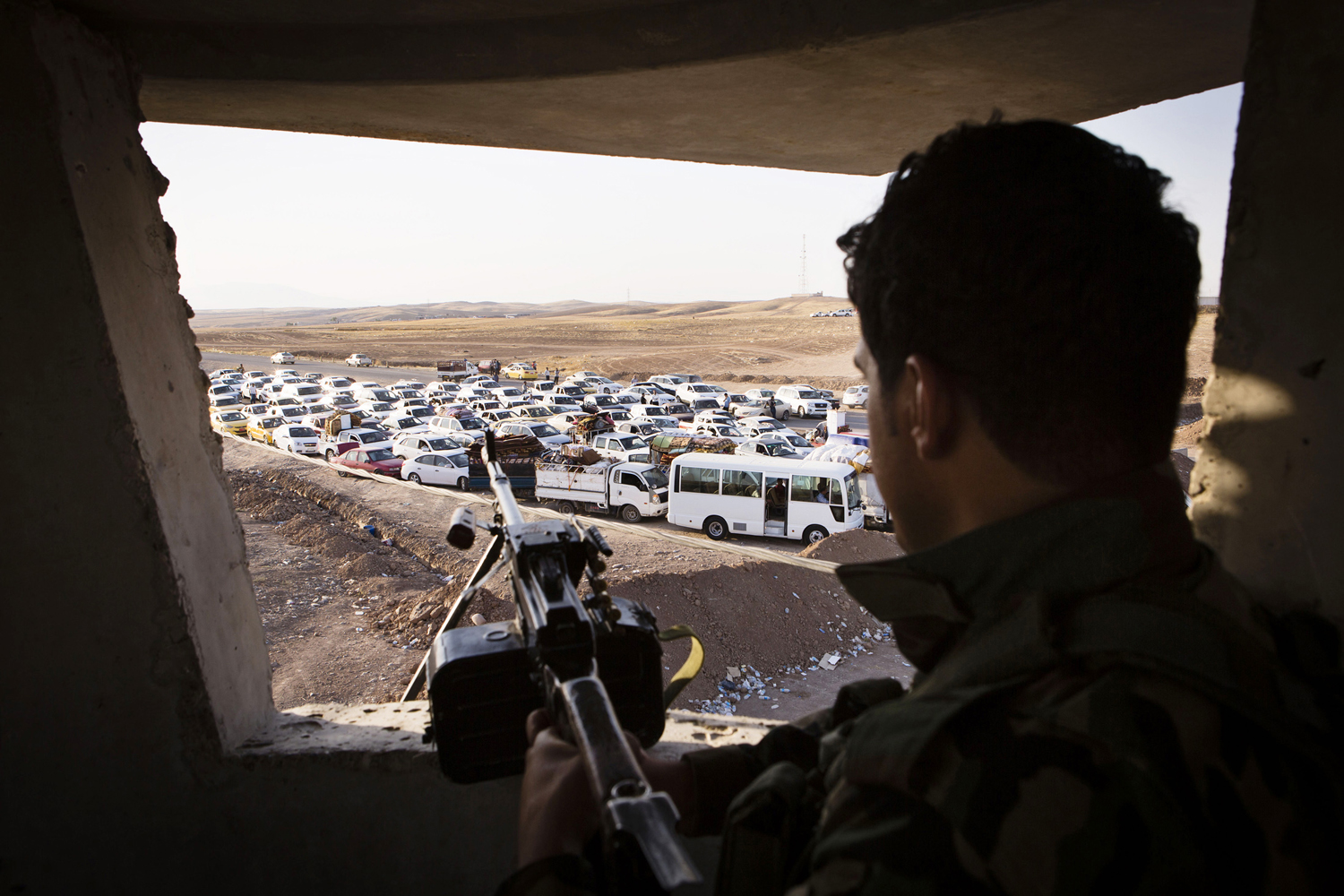 An Iraqi security forces member with his weapon takes position as people, who fled from the violence in Mosul, arrive in their vehicles at a camp for internally displaced people on the outskirts of Erbil in Iraq's Kurdistan region June 14.