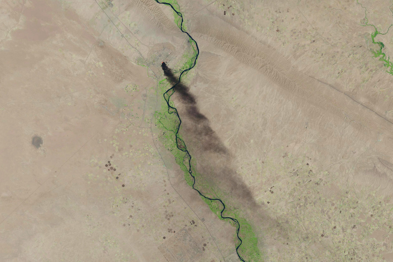 A satellite image shows smoke rising from the Baiji refinery near Tikrit, Iraq, June 18.