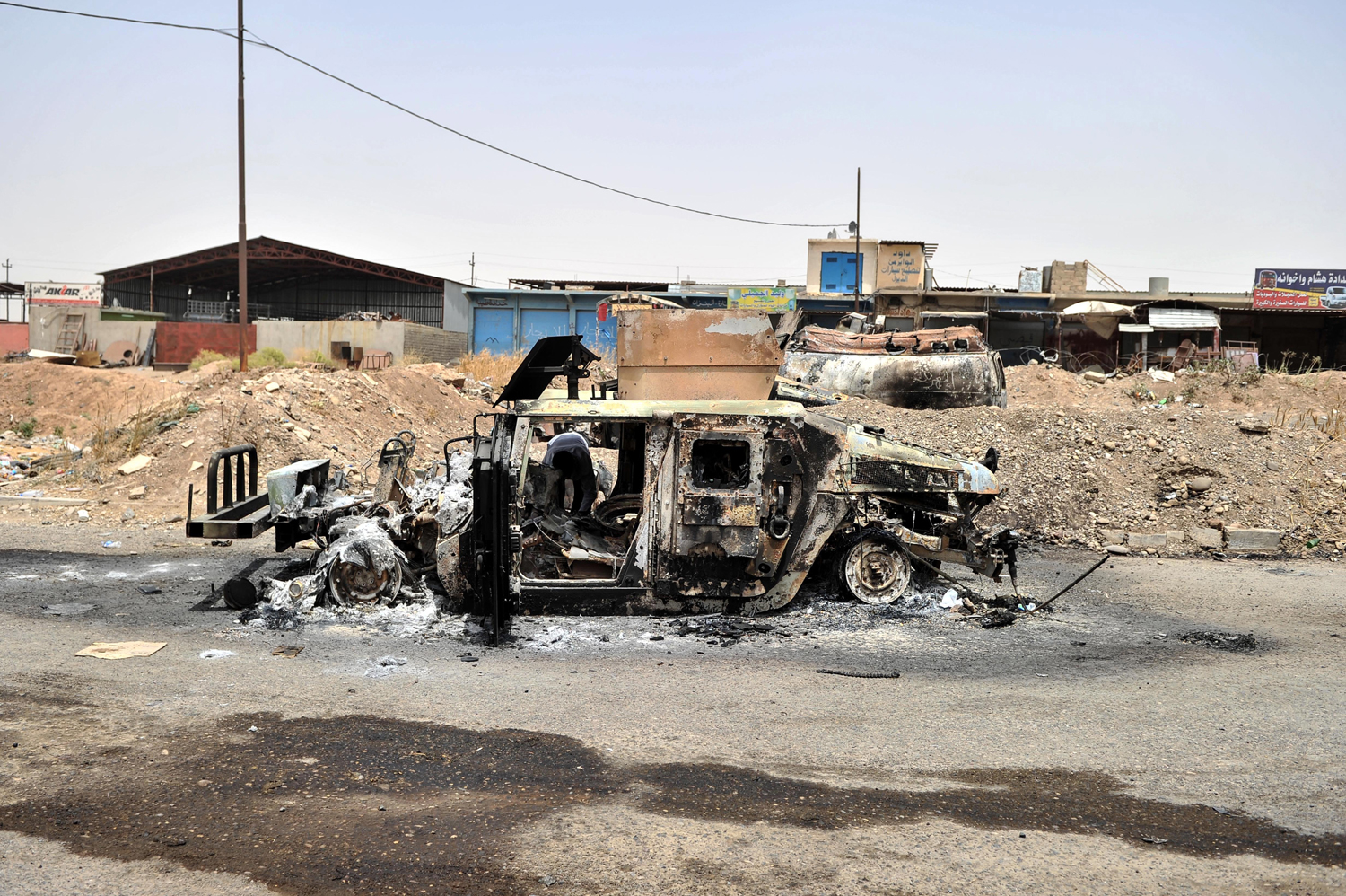 An Iraq army vehicle is burned by militants in Mosul on June 12.