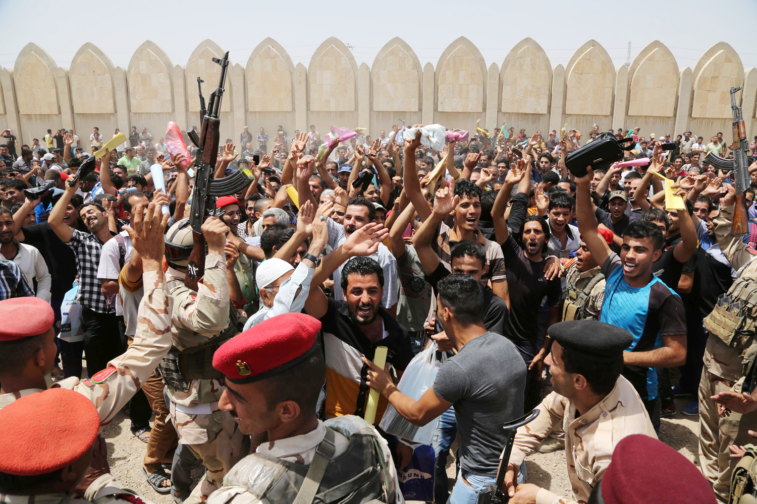 Men chant slogans against the al-Qaida breakaway group Islamic State of Iraq and Syria (ISIS), outside of the main army recruiting center to volunteer for military service in Baghdad on June 12.
