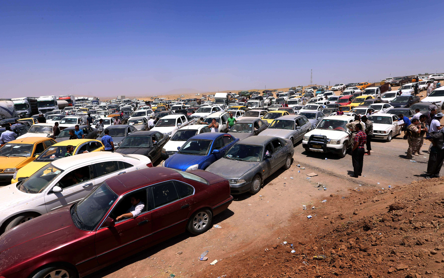 Iraqis fleeing violence in Nineveh province wait in their vehicles at a Kurdish checkpoint in Aski Kalak, 25 miles west of Arbil, the capital of the autonomous Kurdish region of northern Iraq, on June 10, 2014.
