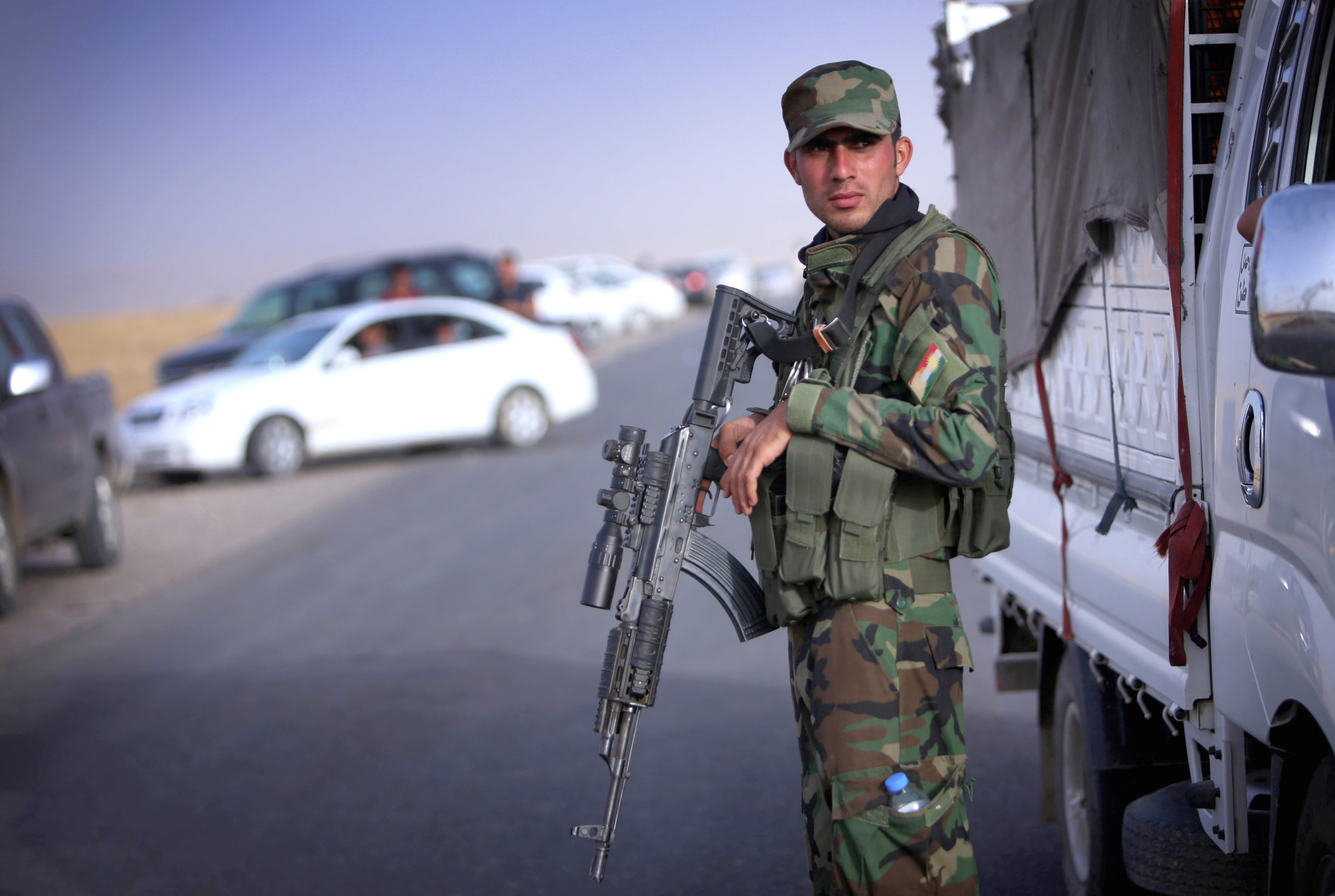 An Iraqi Kurdish security guard stands guard as Iraqi families fleeing violence in the northern Nineveh province gather at a Kurdish checkpoint in the Kurdistan region on June 11, 2014.