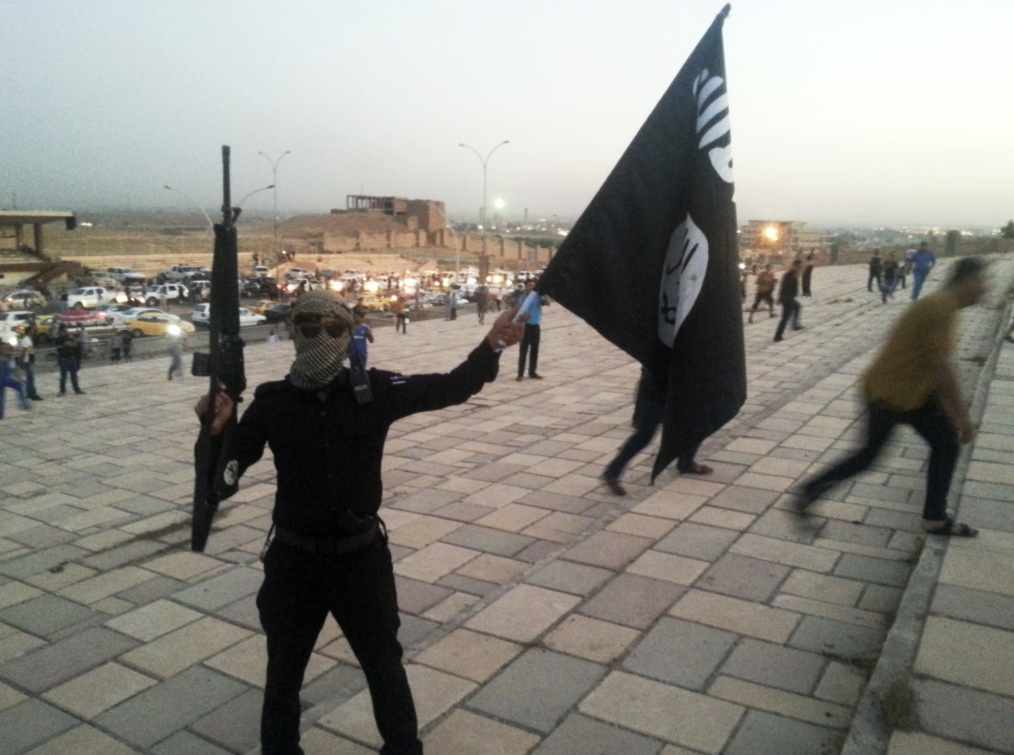A fighter of the Islamic State of Iraq and Greater Syria (ISIS) holds an ISIS flag and a weapon on a street in the city of Mosul, Iraq, on June 23, 2014