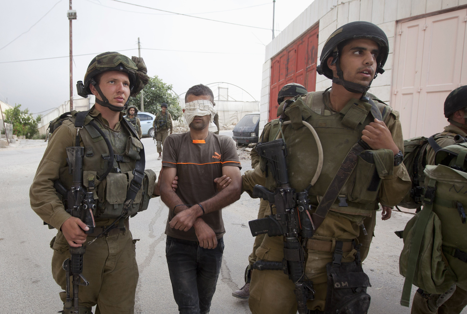 Israeli soldiers arrest a Palestinian man during a search for three missing Israeli teens, feared abducted in the West Bank last week, in the village of Beit Kahil near the West Bank city of Hebron on June 21, 2014.