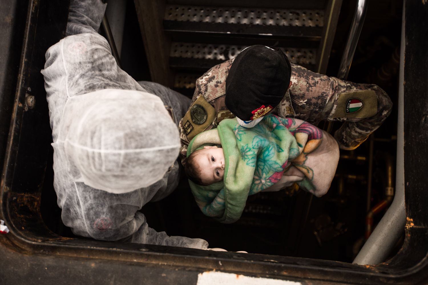 Italian soldier carries a Syrian child on a ship after the Italian navy rescued 443 Syrian asylum seekers off a fishing vessel, June 5, 2014.