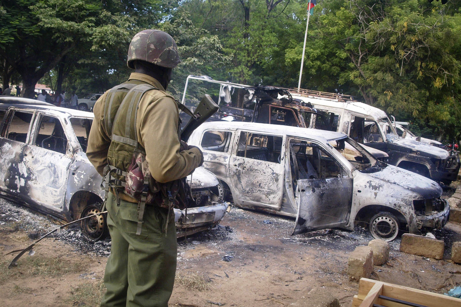 A member of the Kenyan security forces observes the remains of vehicles destroyed by al-Shabab militants in the coastal town of Mpeketoni, about 100 km (60 miles) from the Somali border, on June 16, 2014
