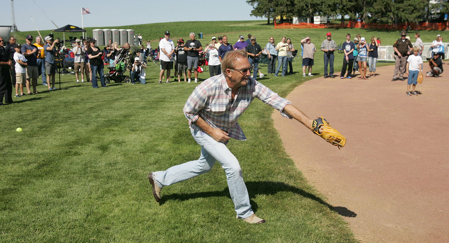 Actor Kevin Costner plays catch with his sons during a party celebrating the 25th anniversary of the  Field of Dreams  movie Friday, June 13, 2014, near Dyersville, Iowa.